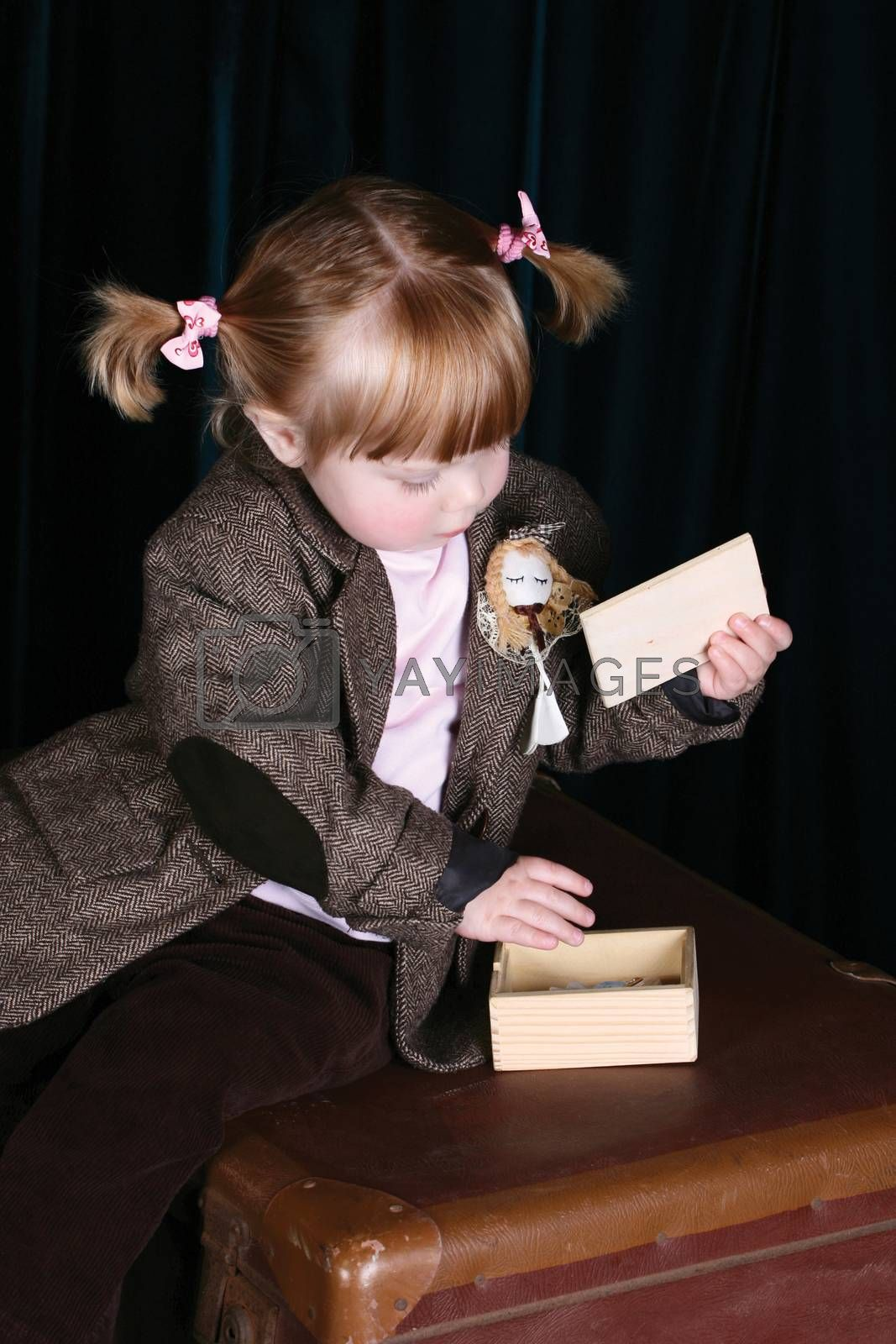 Little girl in vintage attire playing with a puzzle