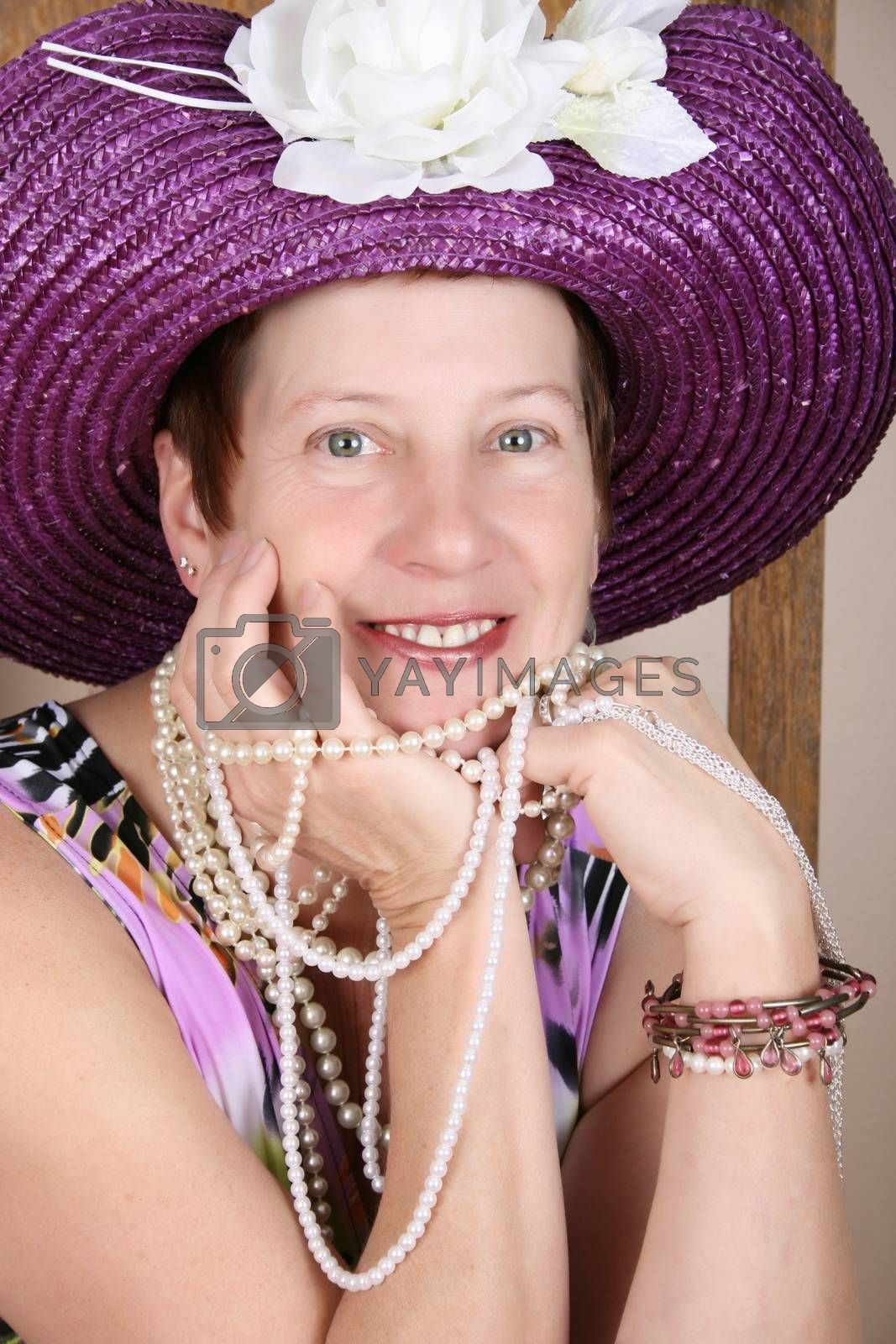Mature female wearing a purple hat and jewellery