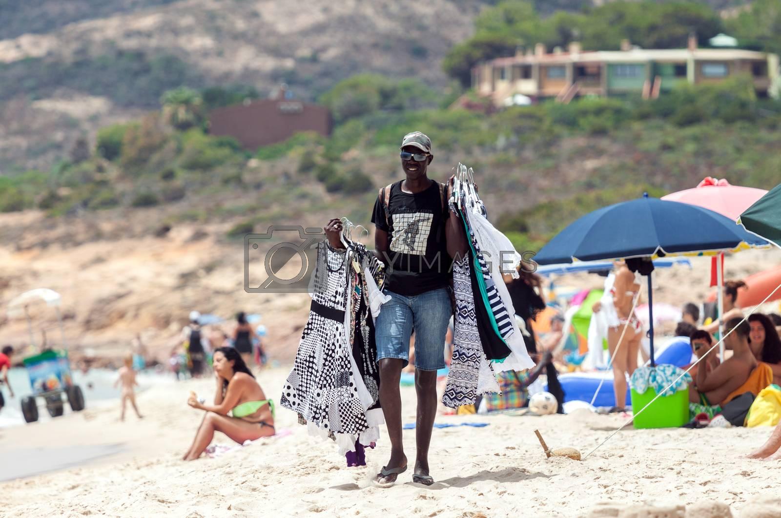SANTA MARGHERITA DI PULA, ITALY - JULY 05, 2016: Black man selling clothes in Santa Margherita di Pula beach in Sardinia, Italy