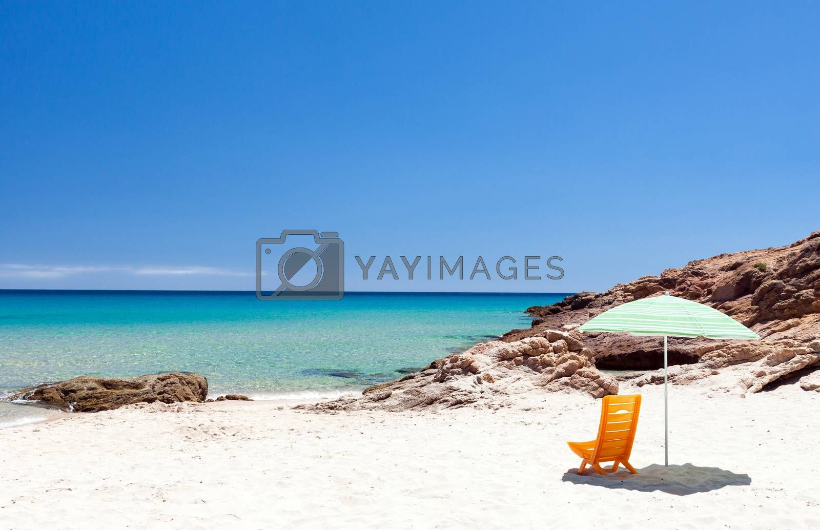 Lonely lounge chair with sun umbrella on a beach in Sardinia, Italy