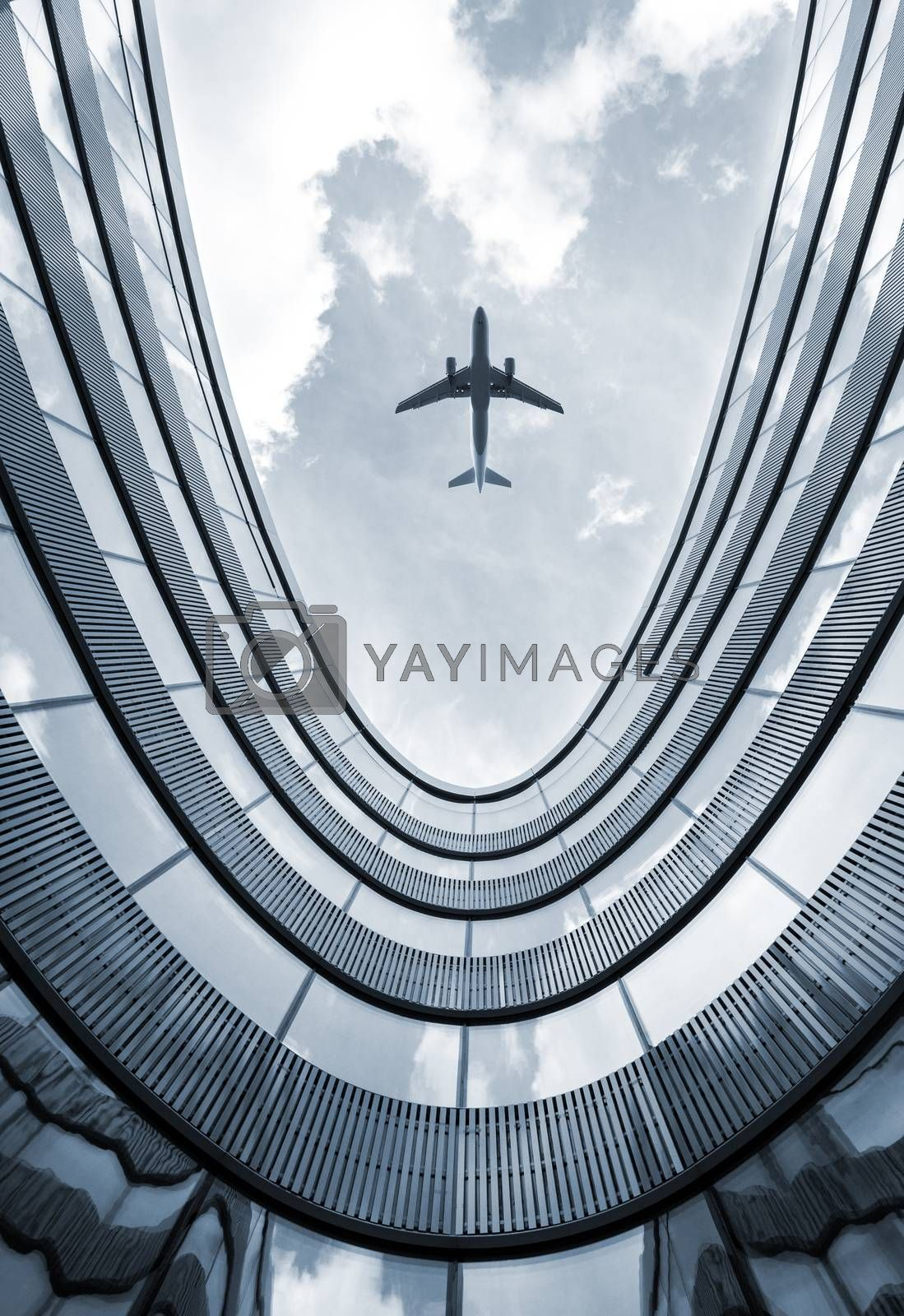 Modern architecture building with flying airplane in background. Low angle view blue colorized picture.