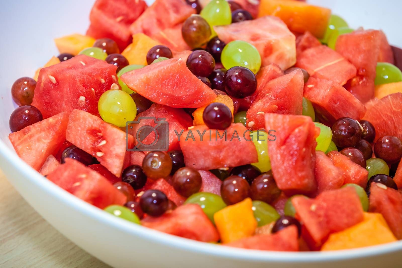 Close up of a large bowl of fresh fruits on a table served for breakfast