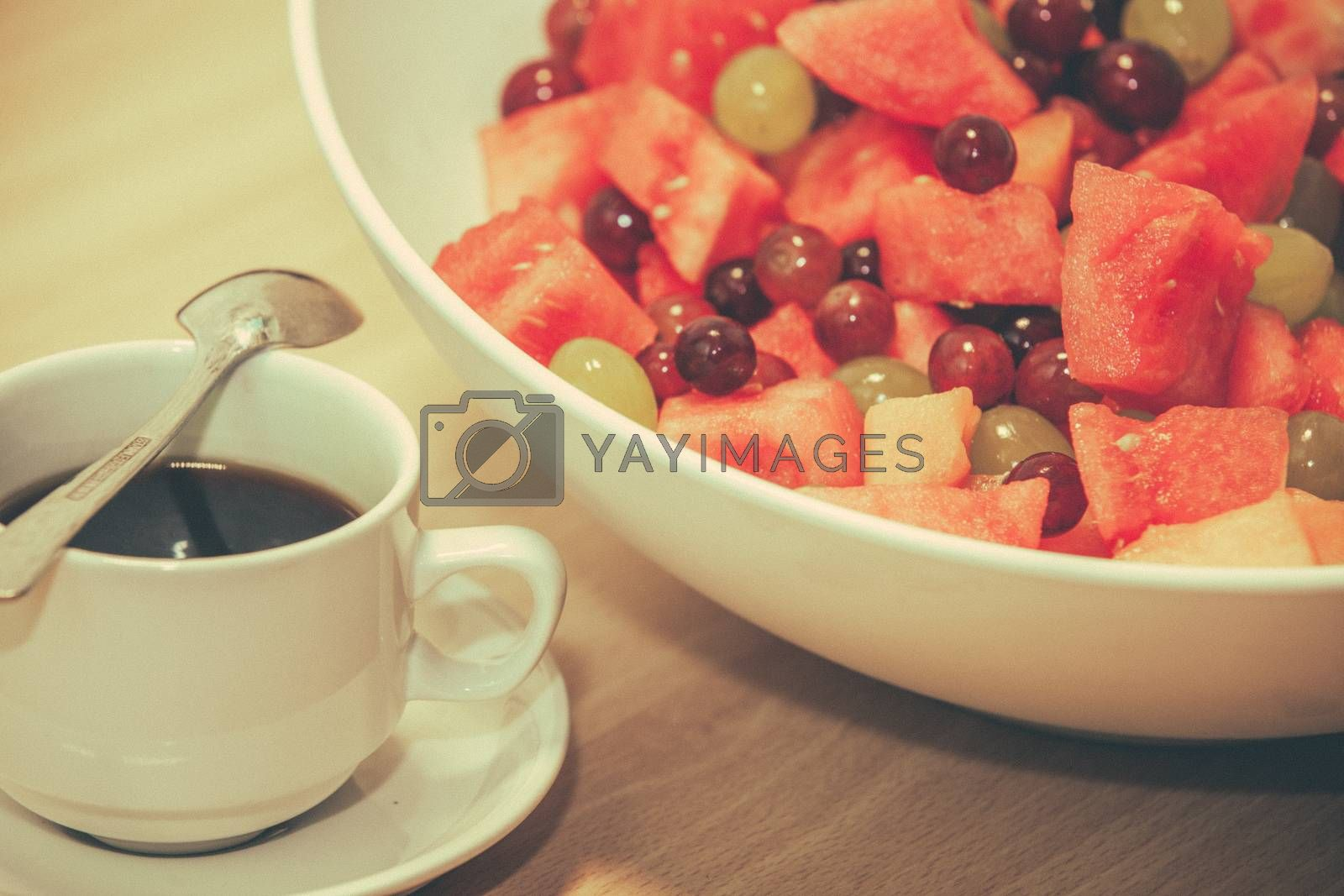 Cup of coffee and bowl of fresh fruits on a table served for breakfast