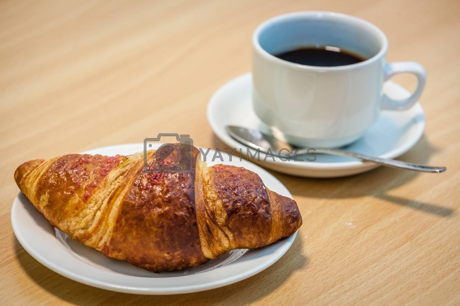 Freshly baked French butter croissant and a cup of black coffee on a table in a restaurant