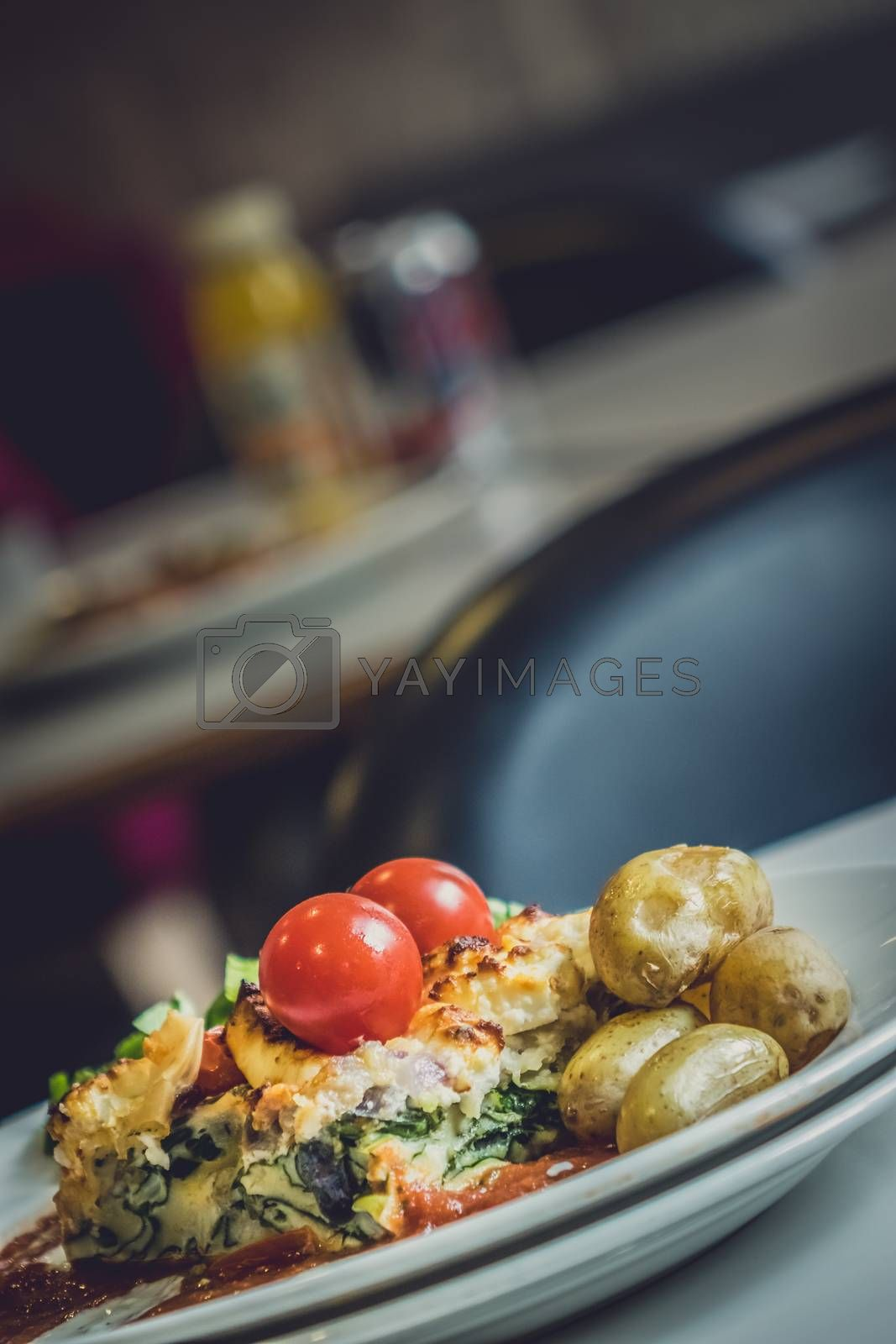 Feta and spinach layered quiche served with tomato sauce, cherry tomatoes and roast potatoes