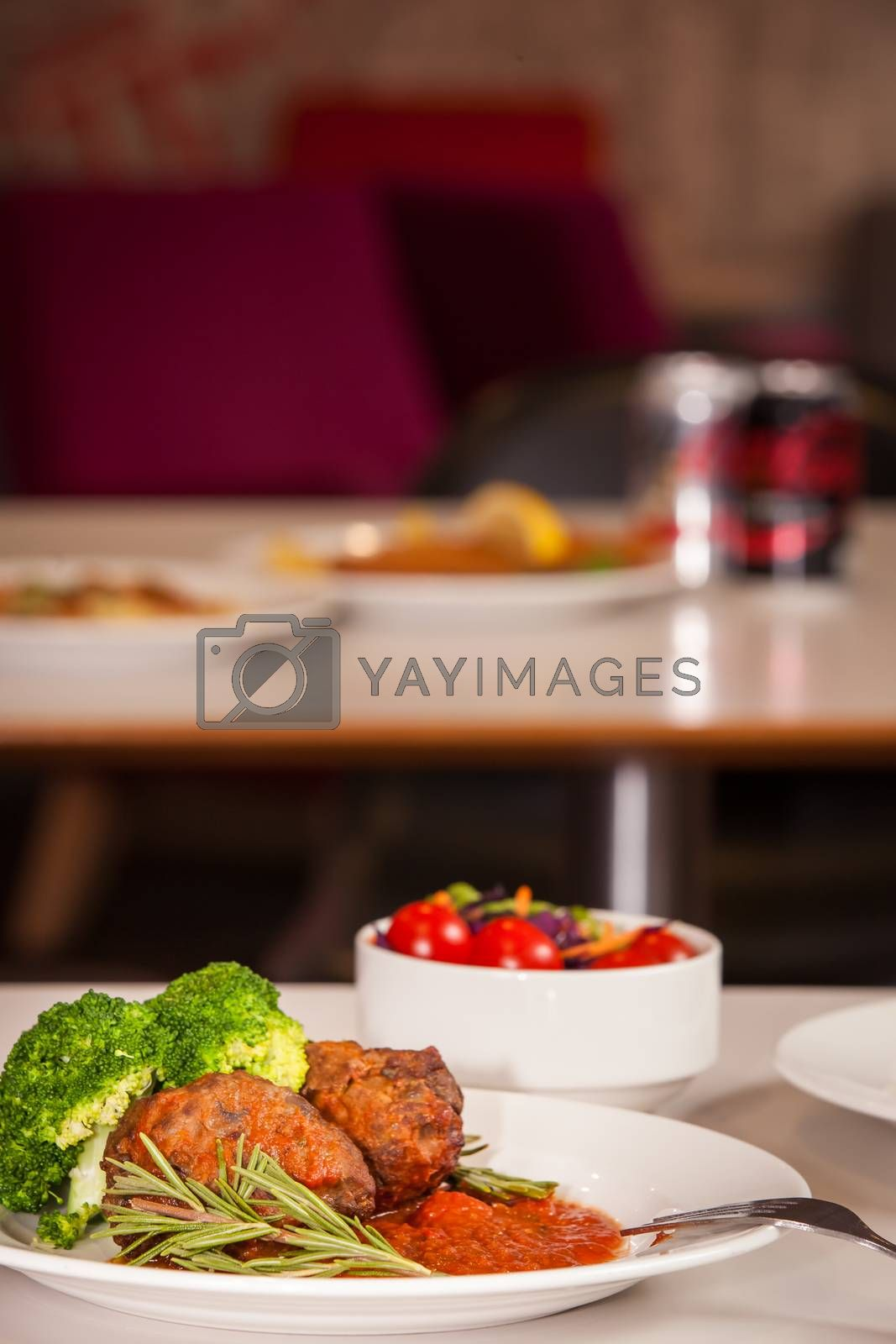 Meatballs with tomato sauce served with broccoli and side salad