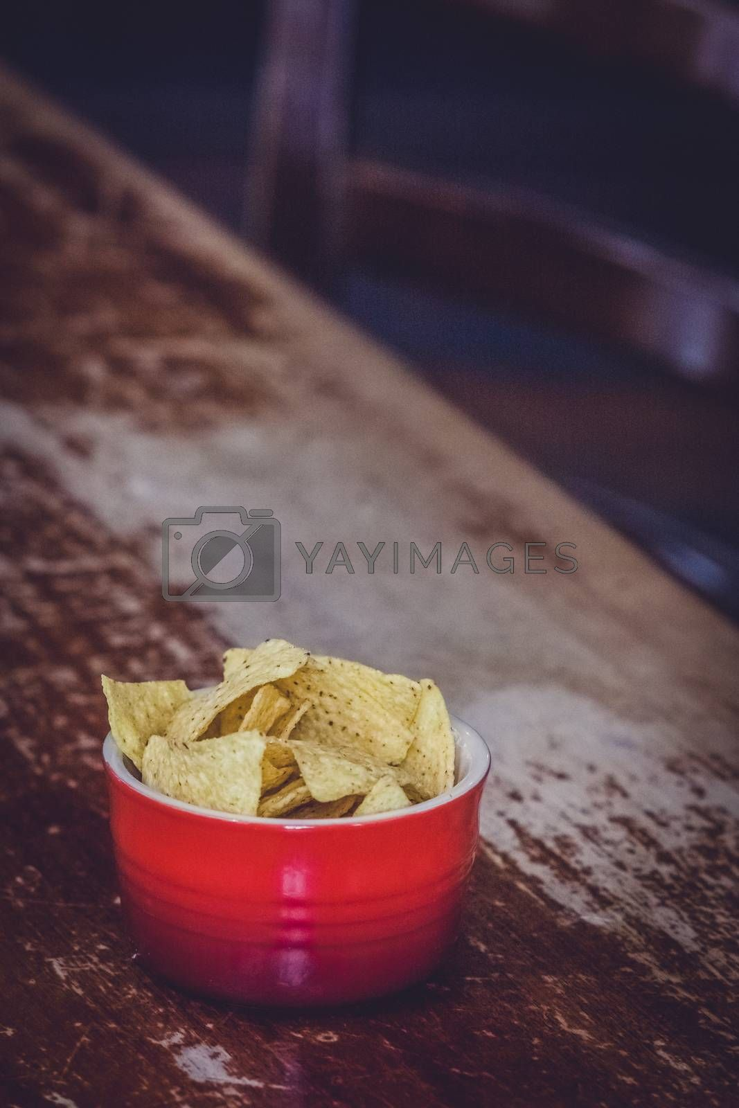 Nachos in red bowl on a table in a pub