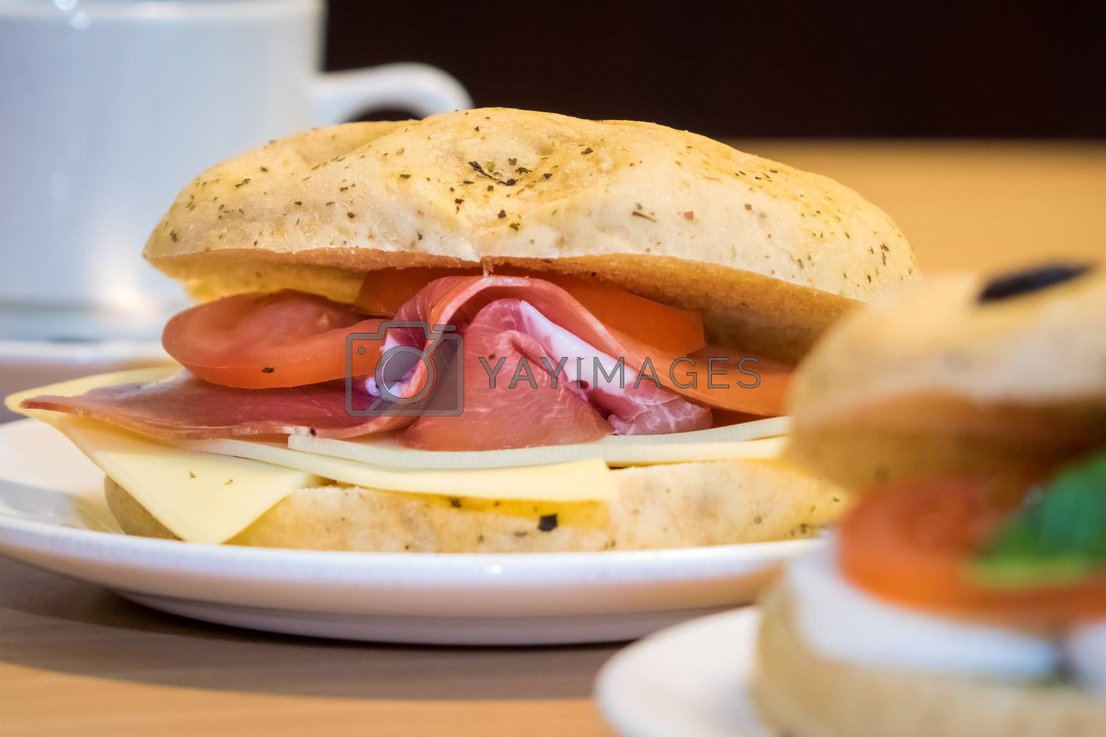 Breakfast bun on a plate, filled with cheddar cheese, prosciutto ham and tomatoes