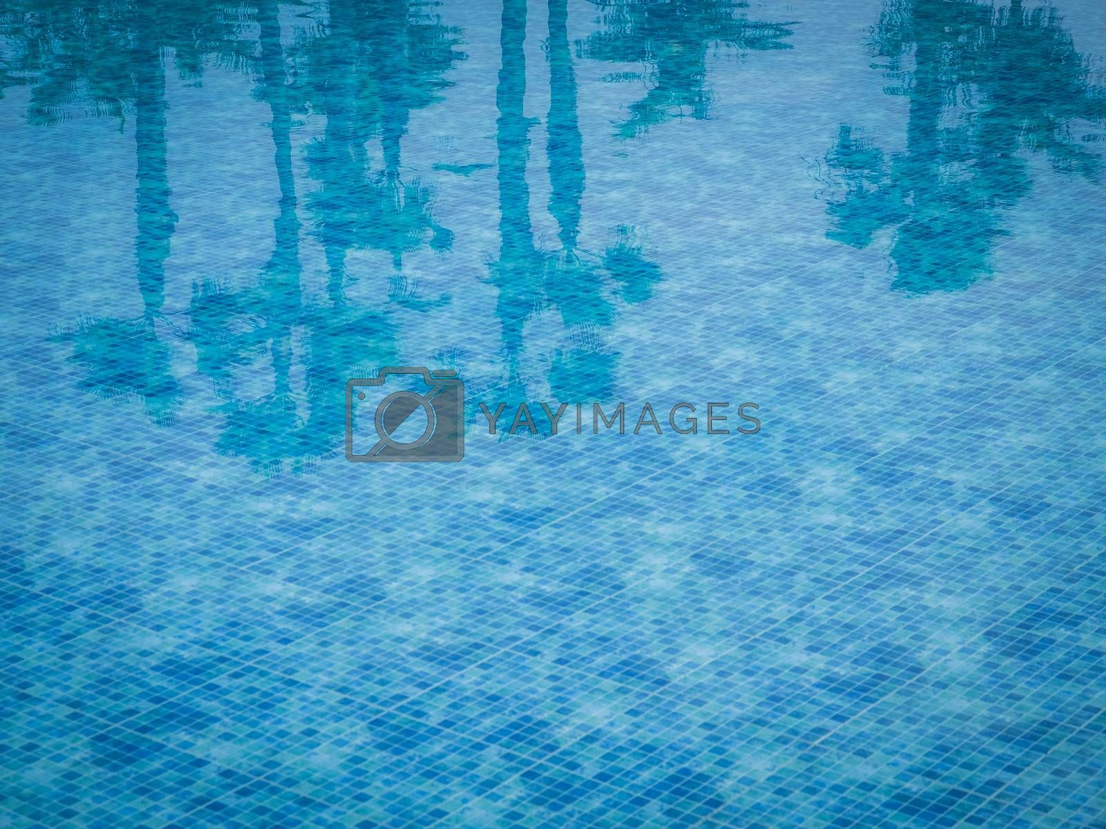 Reflection of few palmtrees in a water of a swimming pool with squared pattern floor tiles