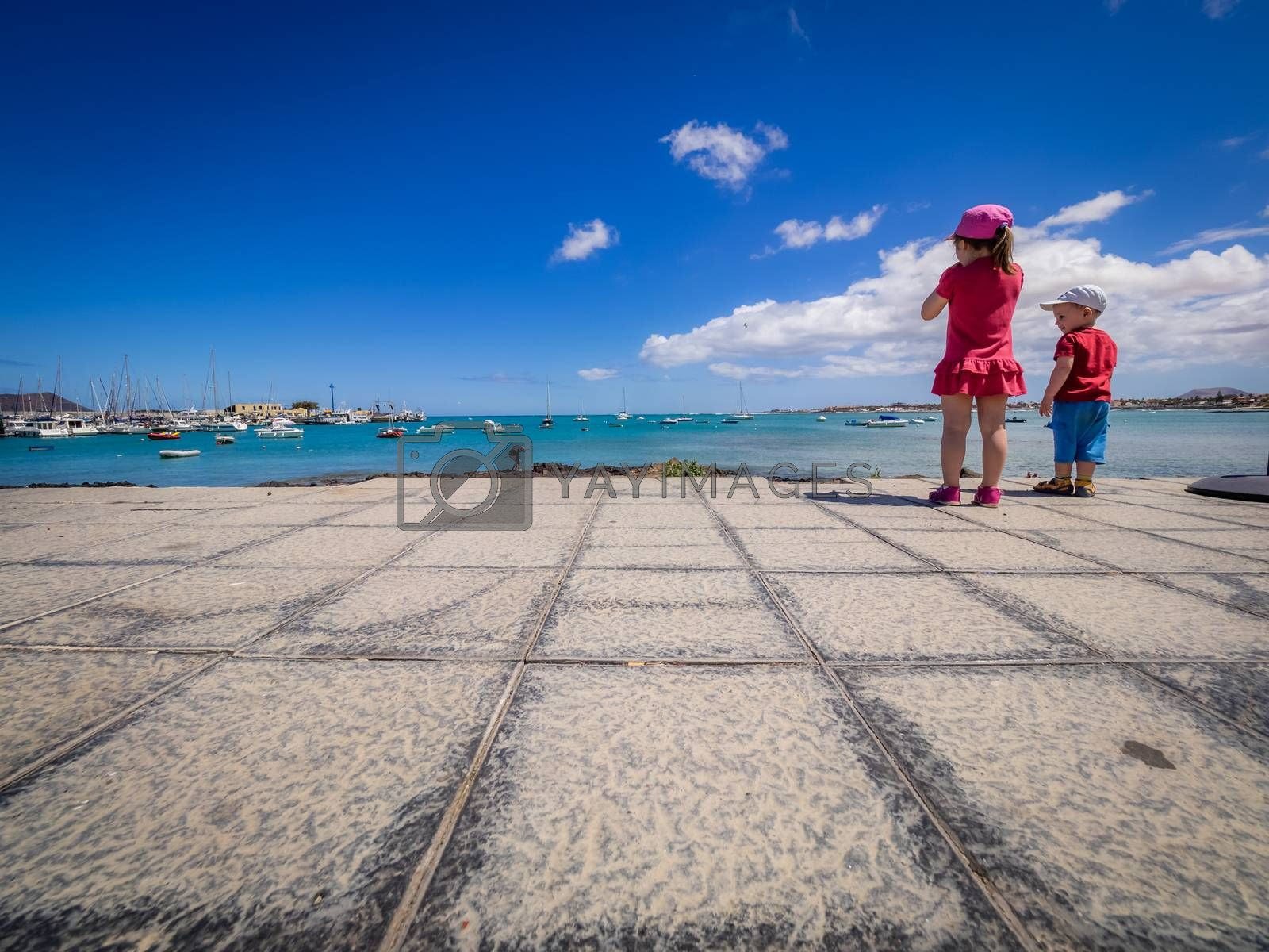 Brother and sister standing on the seaside promenade in the Corralejo harbour, Fuerteventura, Canary Islands, Spain