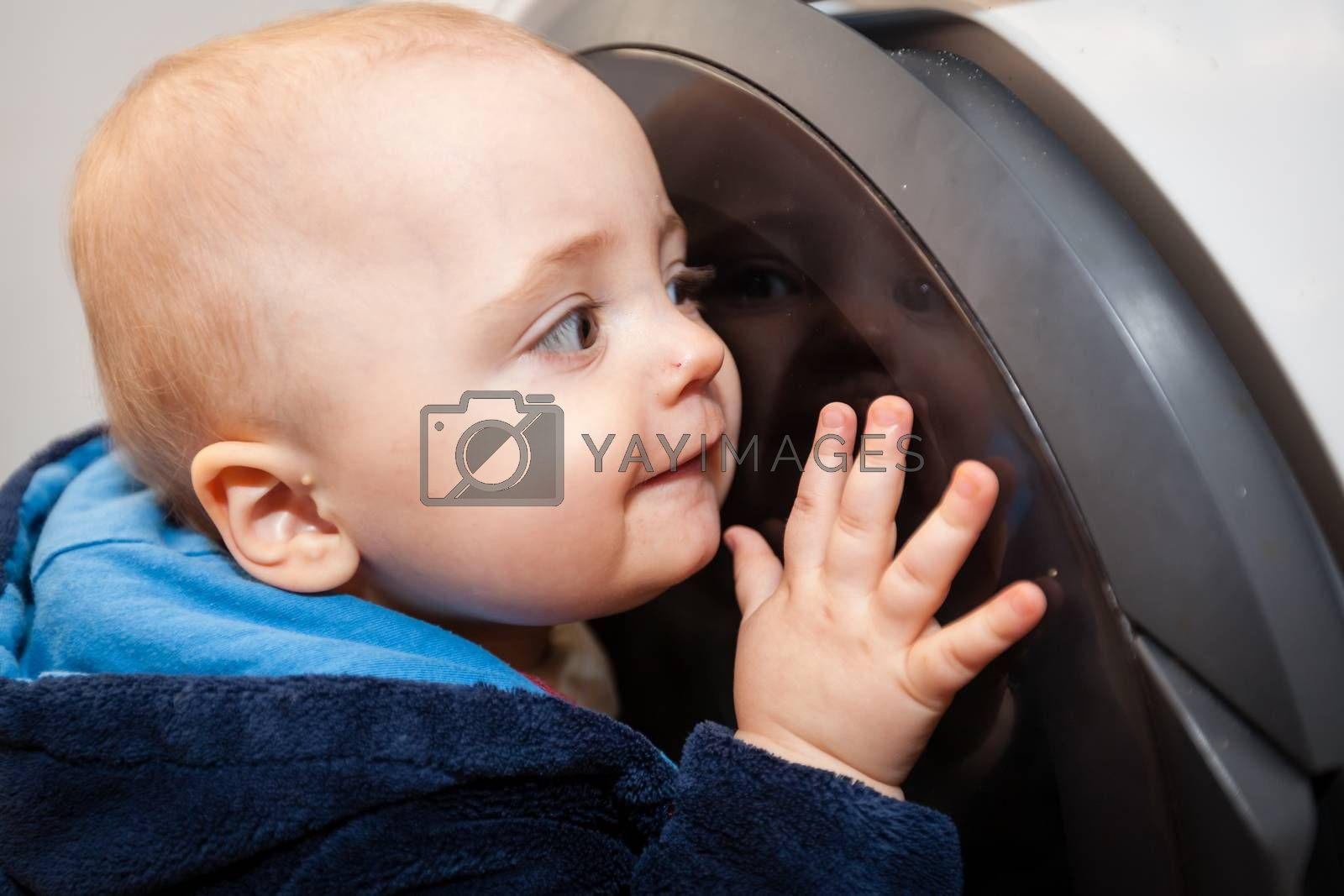 Portrait of a cute little baby boy looking with fascination inside the washing machine