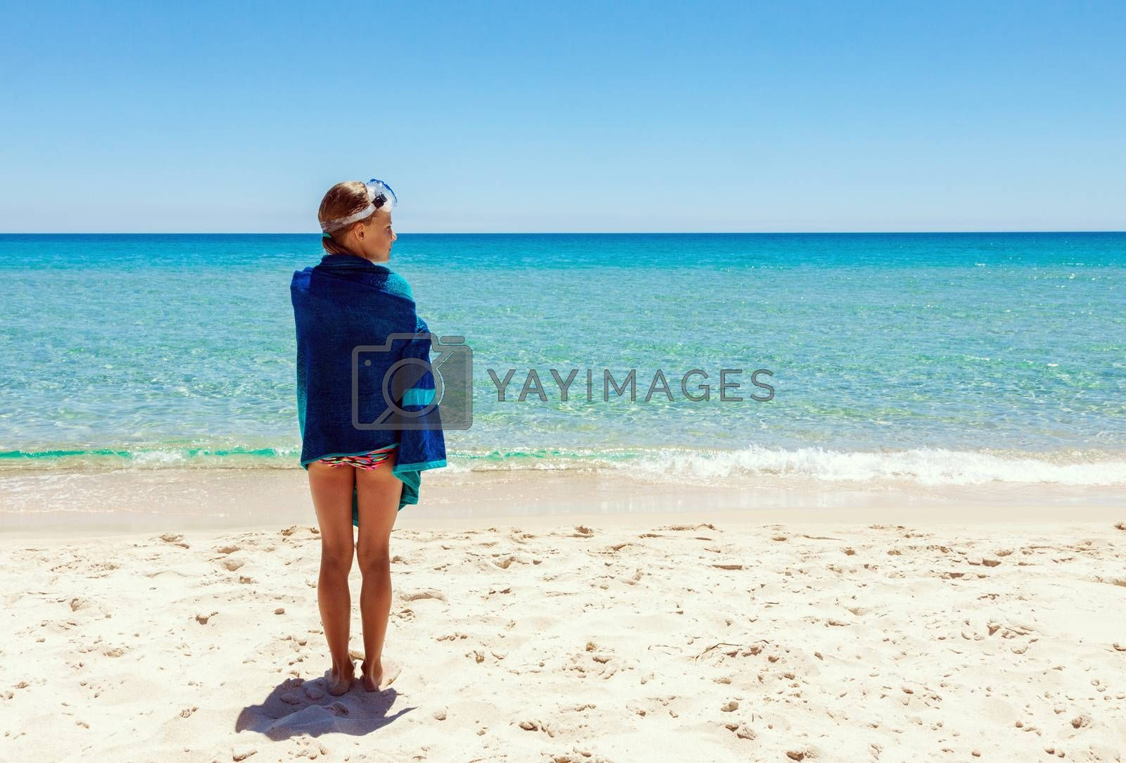 Young teenage girl standing alone on the beach at summer. Covered with towel and wearing snorkel glasses on her head.