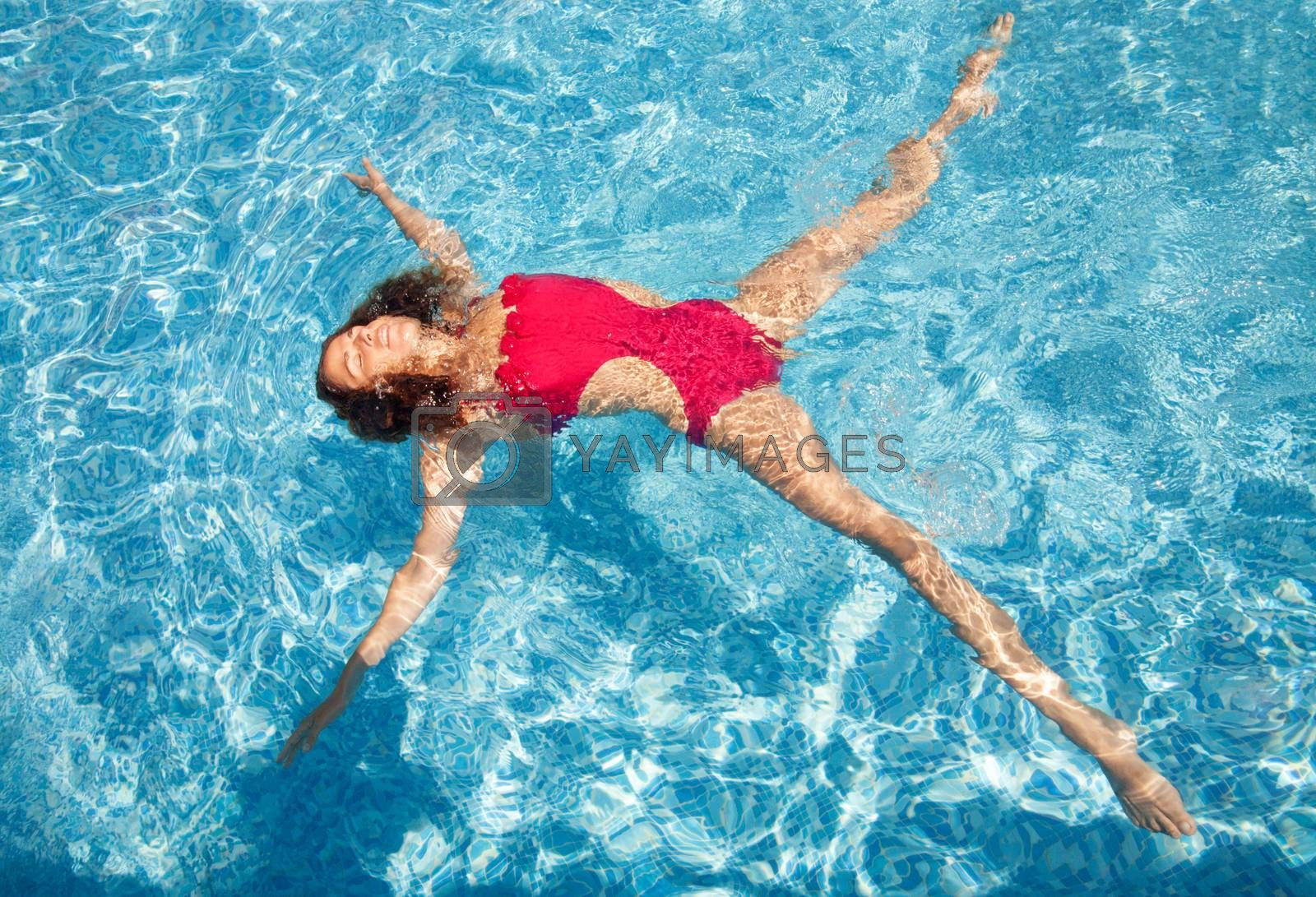 Beautiful young woman laying back on water in pool, star position - relaxed under the sun.