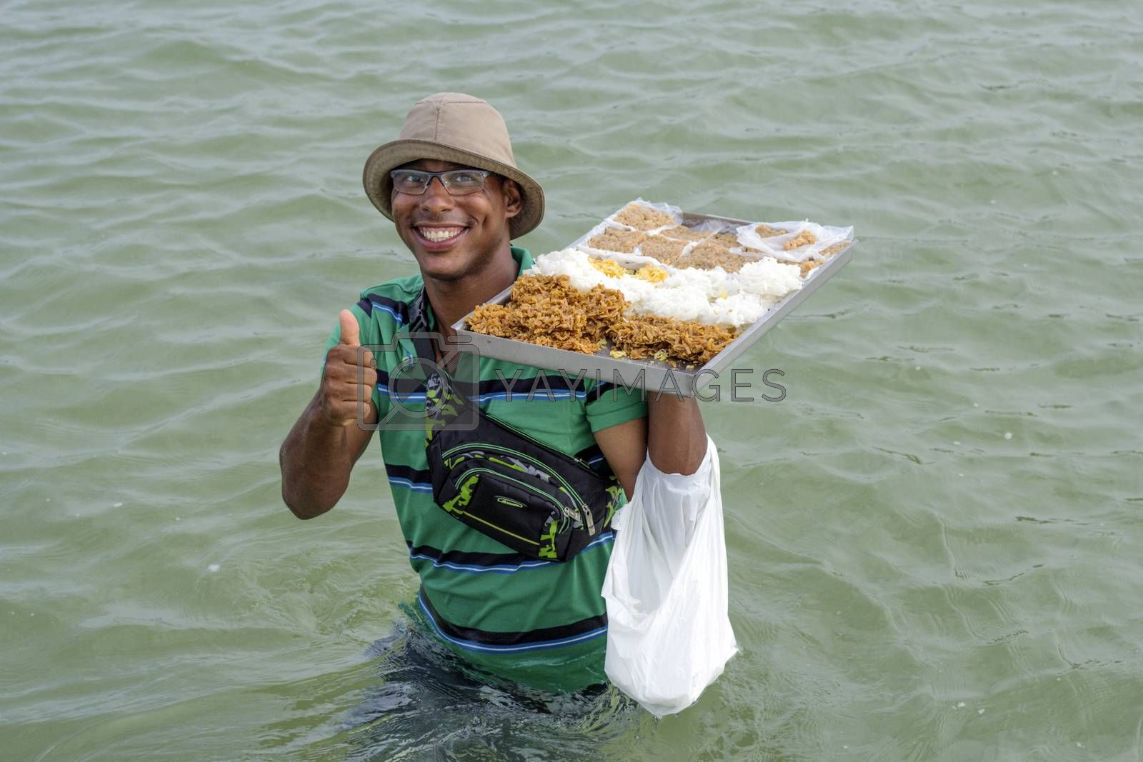 Pernambuco, Brazil July 6, 2016: An unidentified coconut sweet vendor in Chicken Beach with typical sail boats in Ipojuca City near barrier reef, northeast Brazil