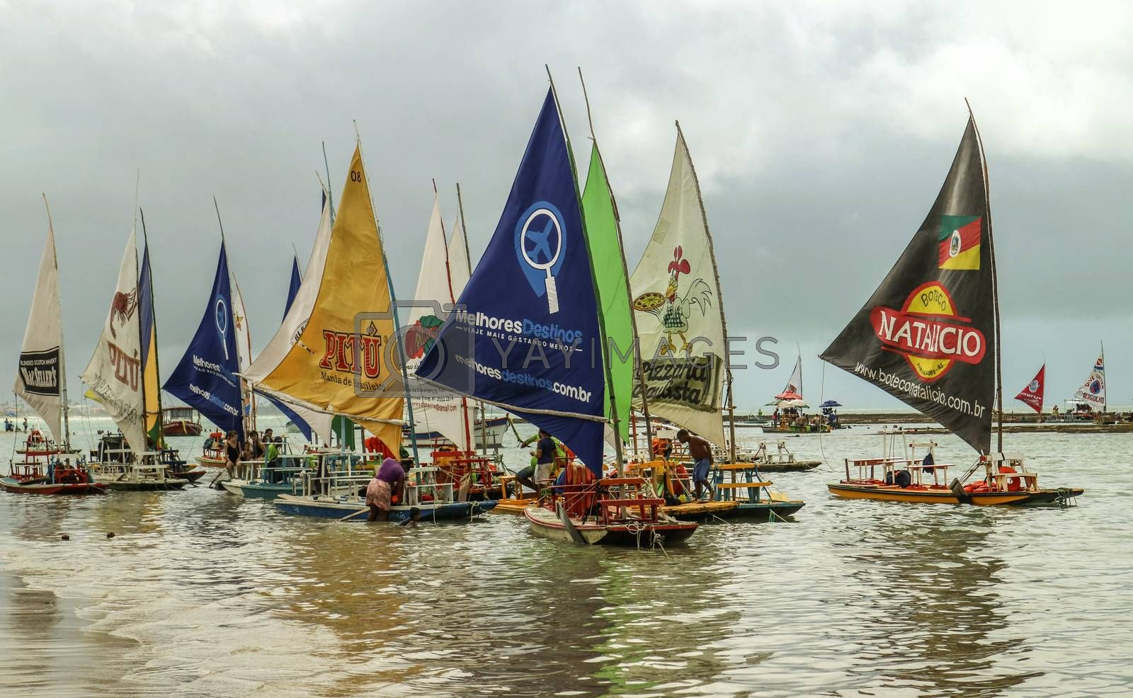 Pernambuco, Brazil July 6, 2016: An unidentified group of people in Chicken Beach with typical sail boats in Ipojuca City, northeast Brazil