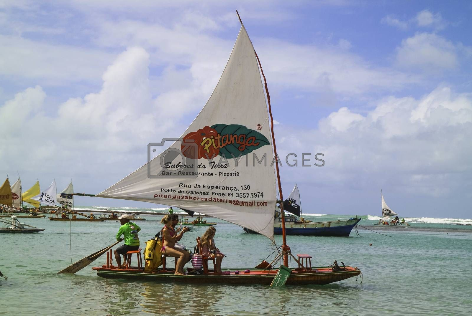 Pernambuco, Brazil July 6, 2016: An unidentified group of people in Chicken Beach with typical sail boats in Ipojuca City near barrier reef, northeast Brazil