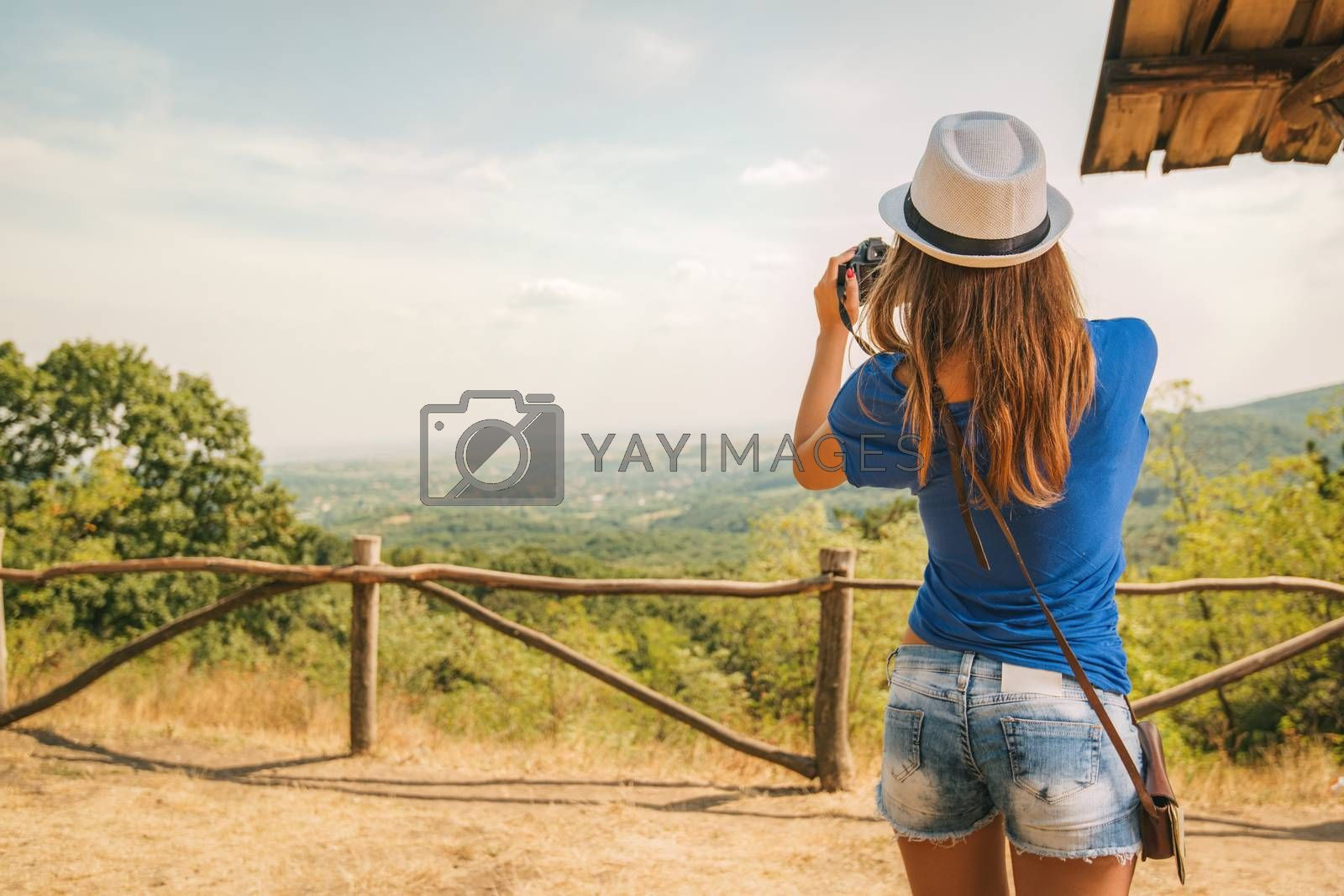 Young beautiful woman standing by viewpoint and taking photo for memory.