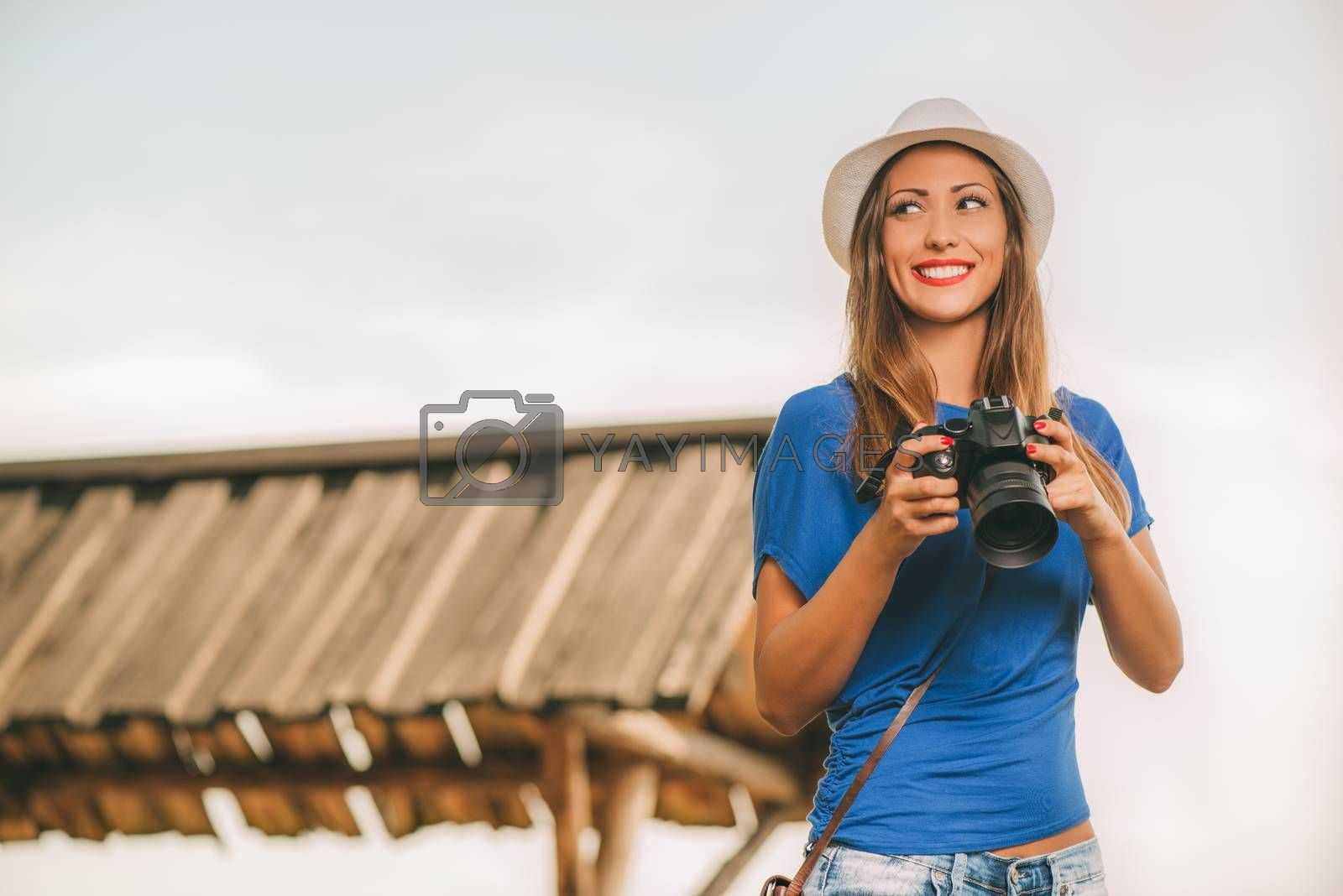 Young beautiful woman standing by viewpoint and holding digital camera.