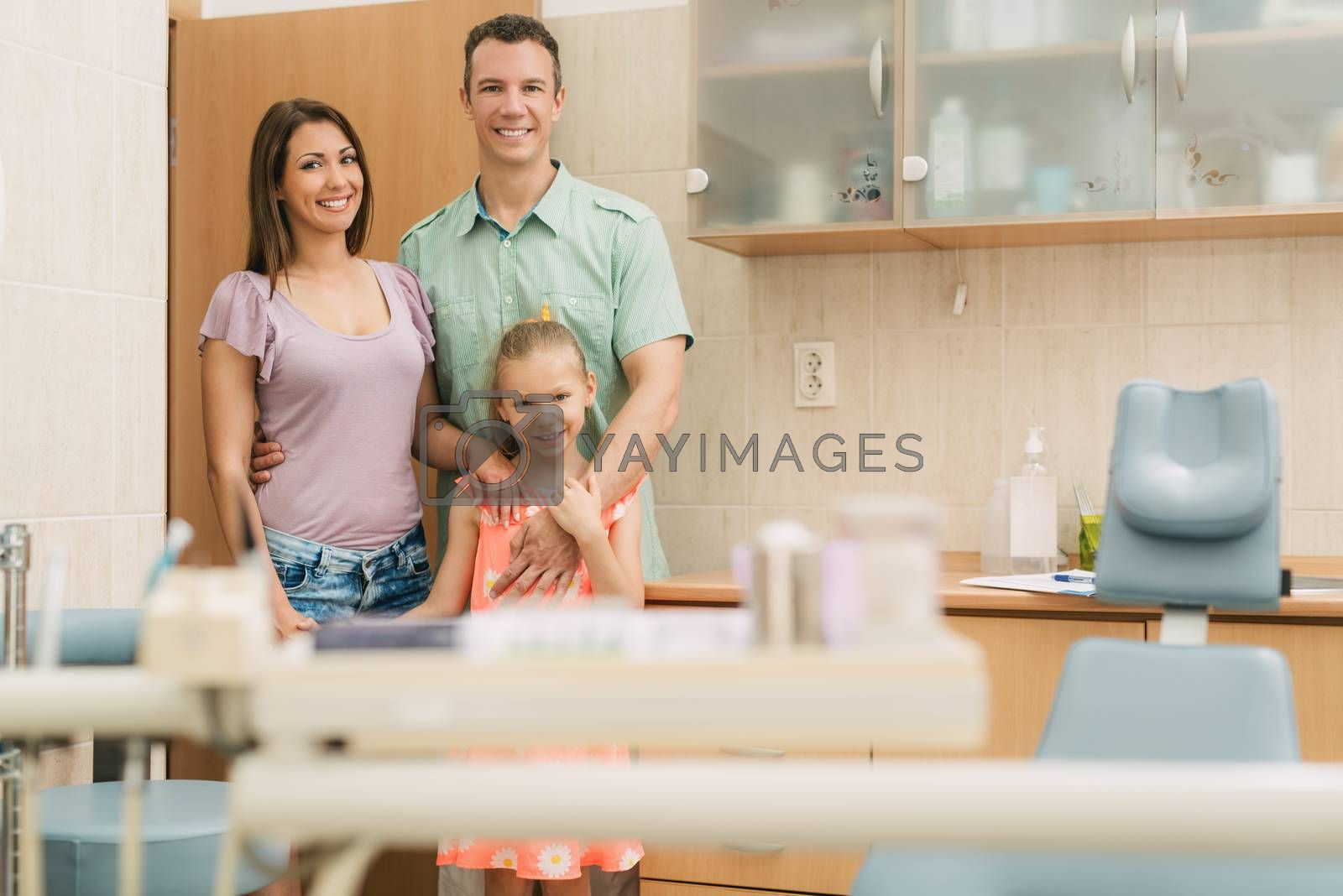 Happy young family at visit in the dentist office. They are standing and looking at camera.