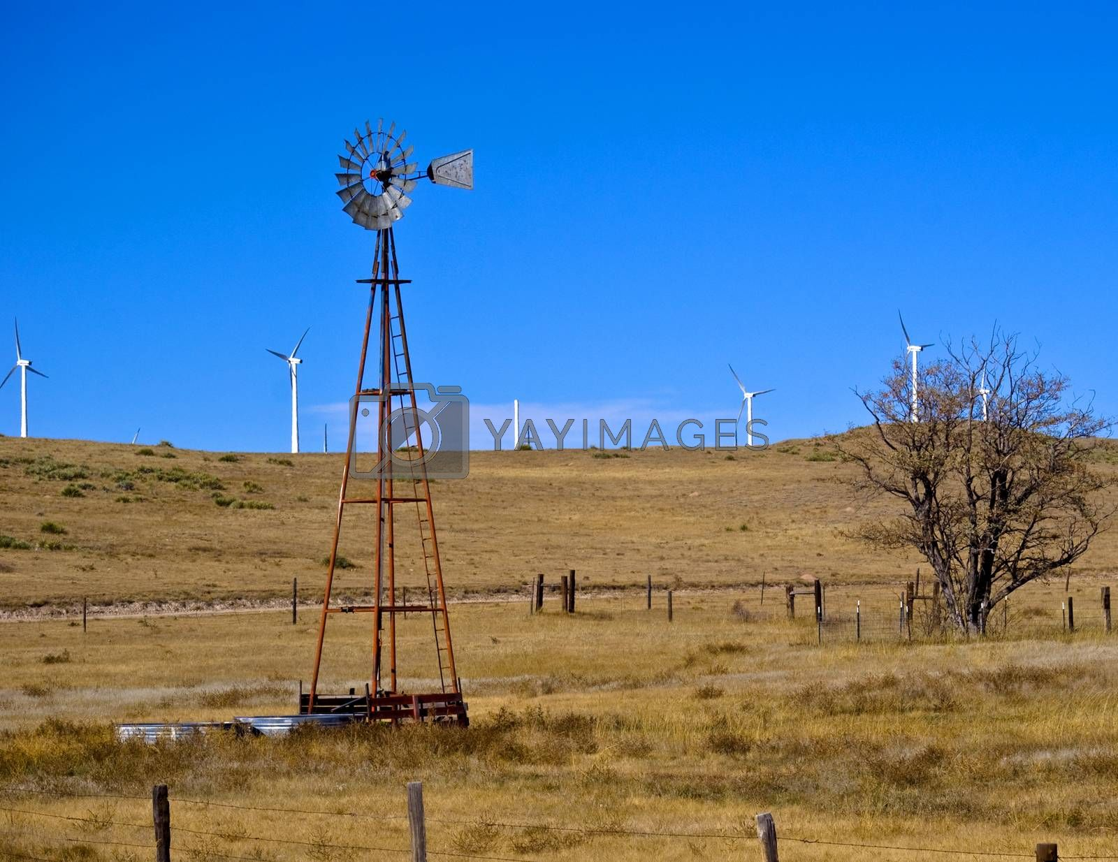 An old wind driven water well is surrounded by new wind generators.