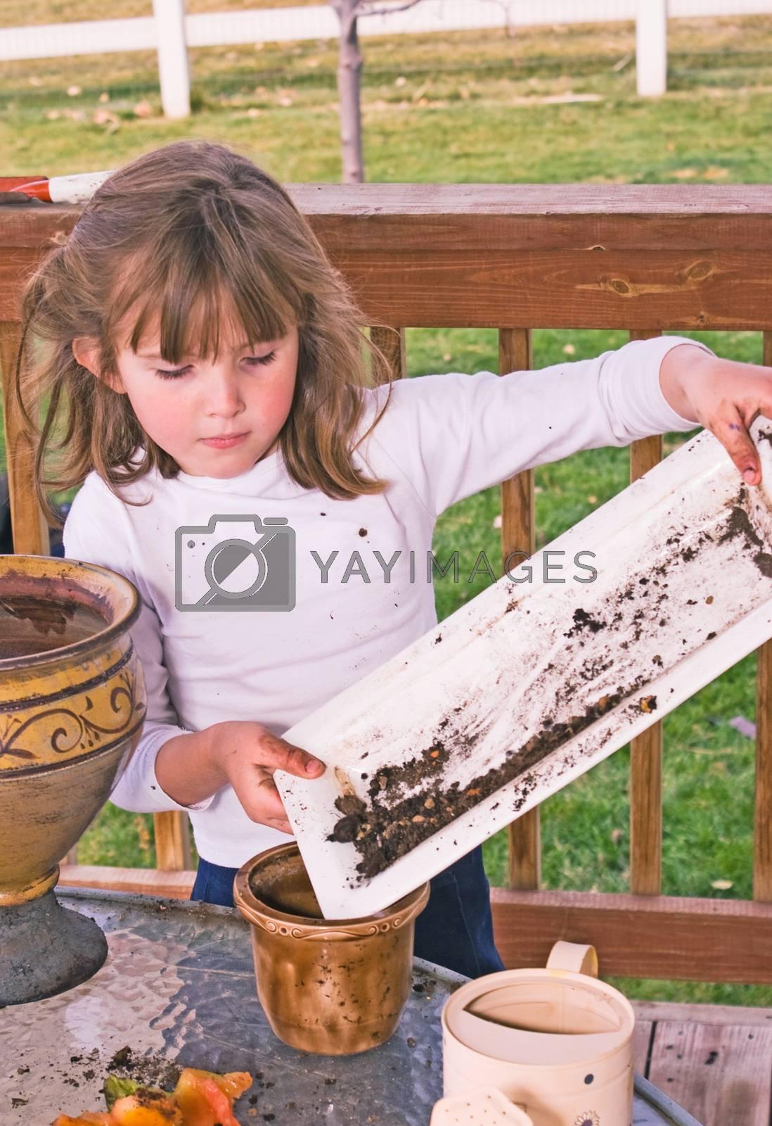 Little girl helping grandma replant new flowers.