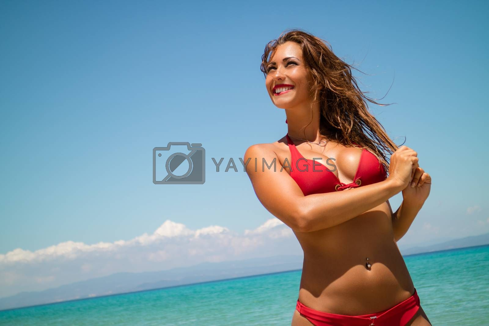 Portrait of a beautiful young woman enjoying on the beach. She is smiling and looking away.