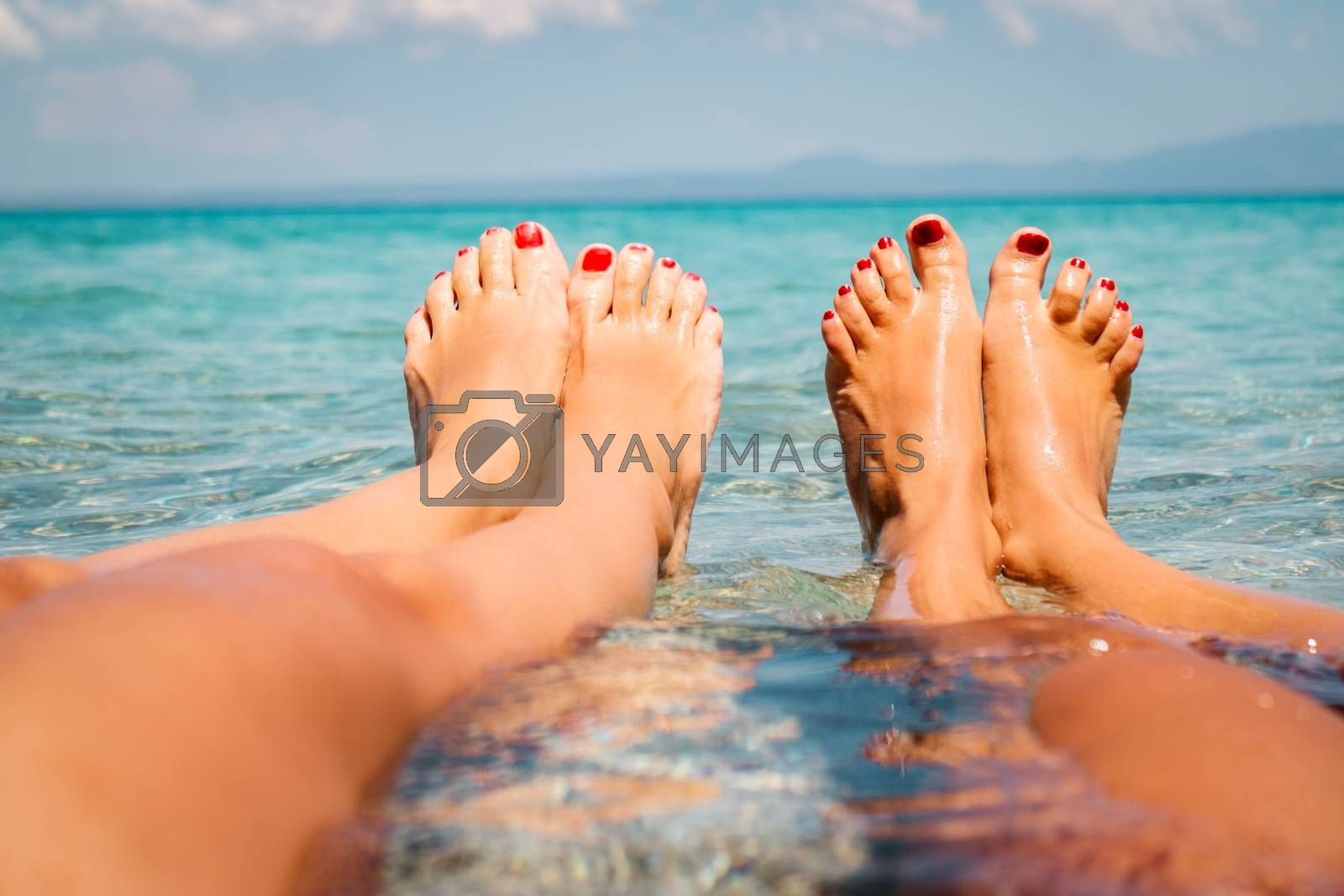 Two girlfriends enjoying on the beach. They are lounging with legs in the sea. Close-up on the womans legs.
