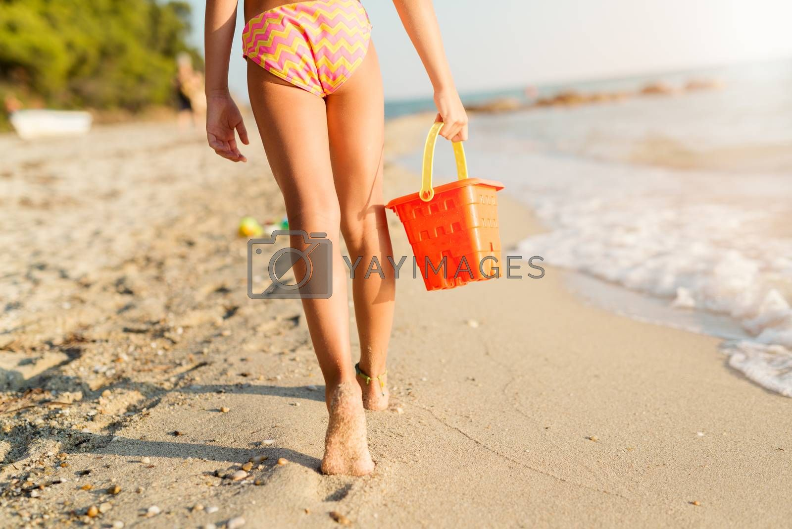 Little girl walking on the beach with bucket. Rear view.
