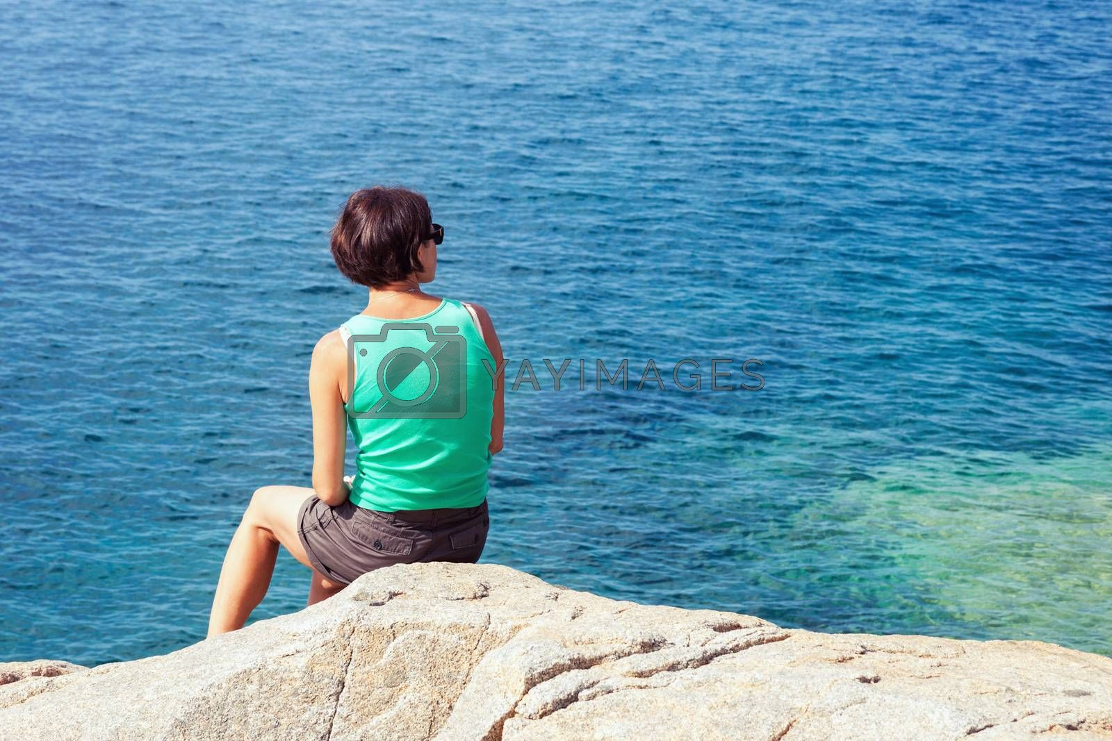 Young caucasian woman sitting on the rock and looking at blue sea. Woman seen from behind, plenty of copy space on the right.