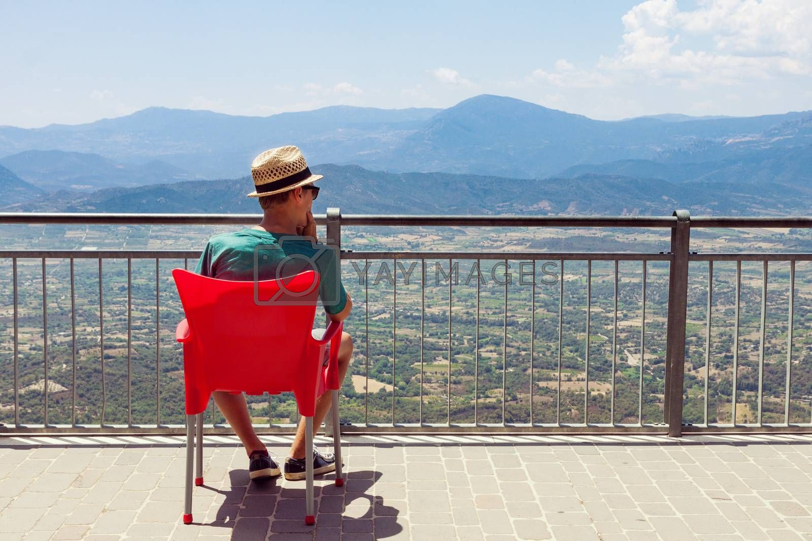 Teenager sitting on red chair and looking at the mountainous view in Sardinia, Italy. Picture with copy space on the right