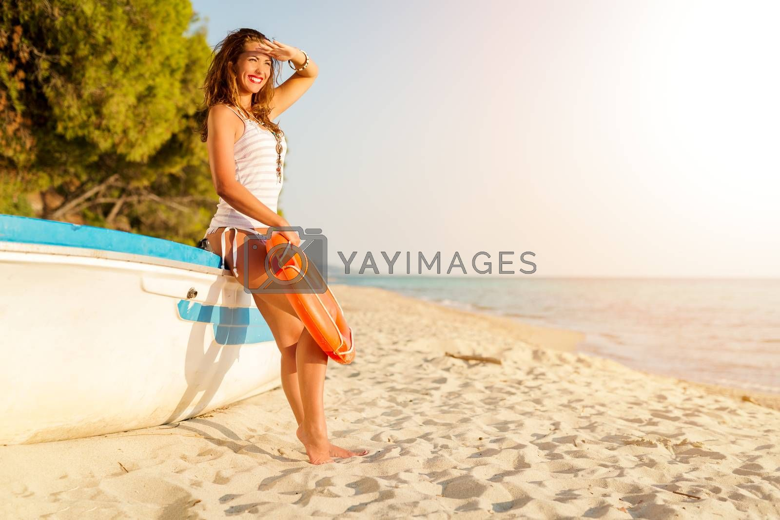 Beautiful young woman relaxing on the beach. She is standing next to boat and looking away.