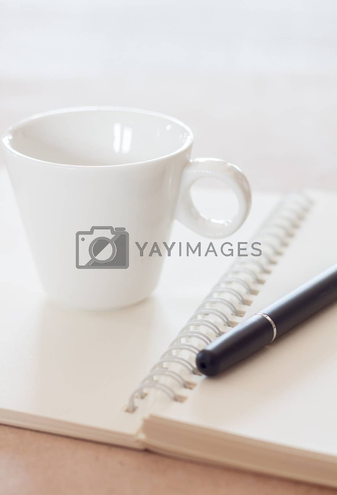 Pen and spiral notebook with coffee cup, stock photo