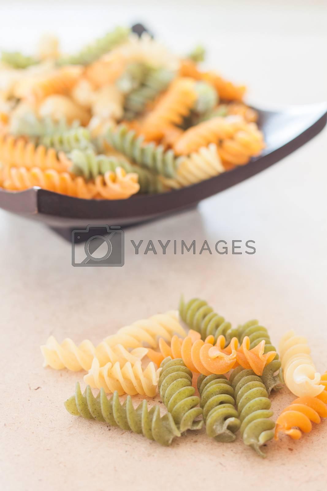 Raw fusilli pasta on wooden tray, stock photo