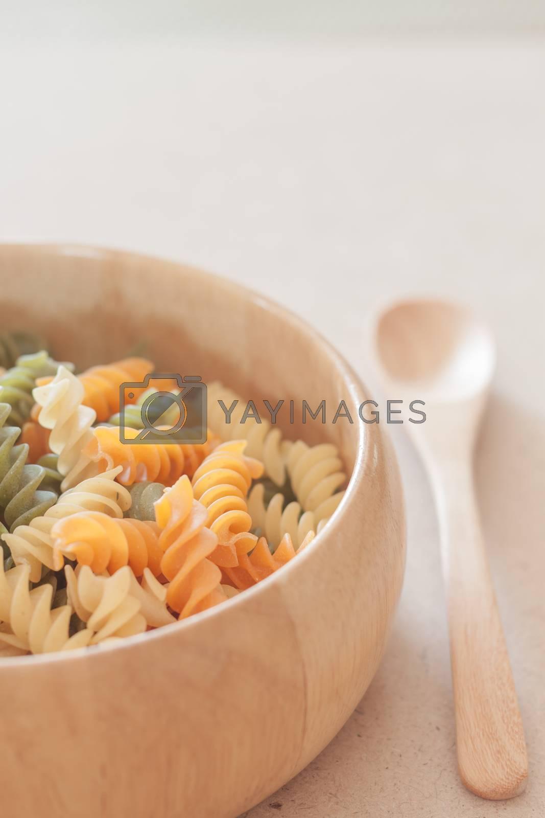 Raw fusilli pasta on wooden bowl, stock photo