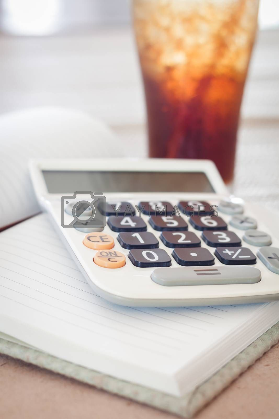 Calculator on blank notebook with a glass of cola, stock photo