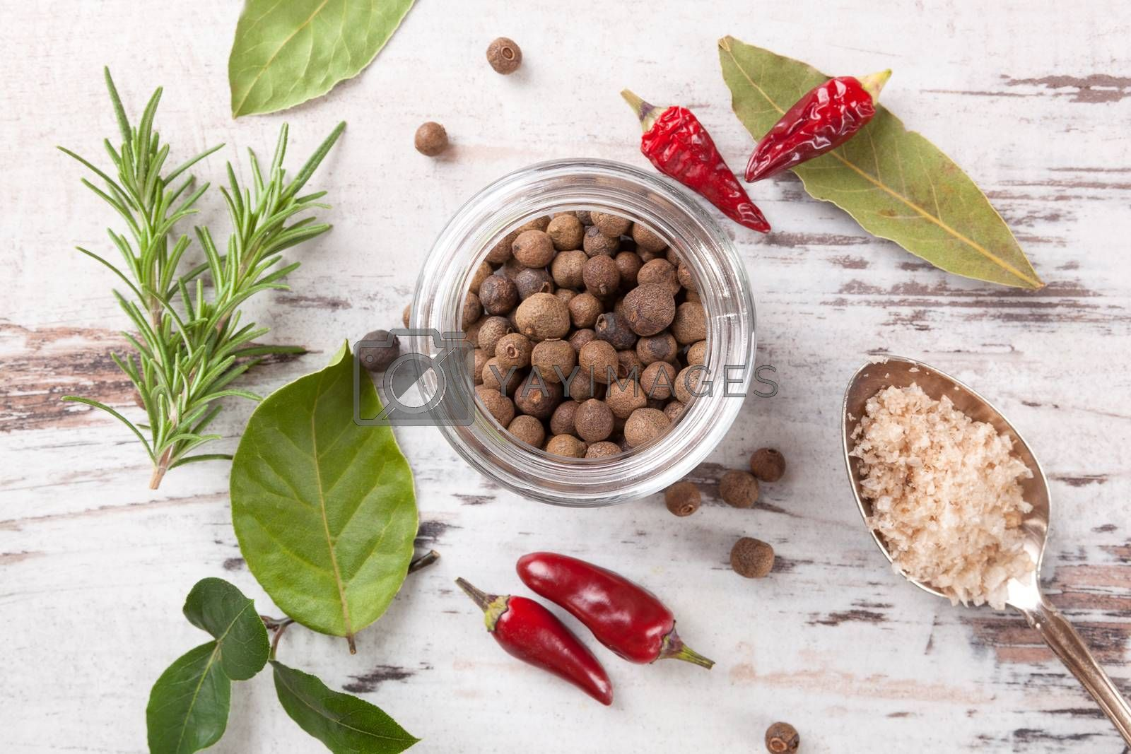 Traditional spice and condiment on white wooden background. Bay leaves, rosemary, chillies and black pepper on wooden table, top view.