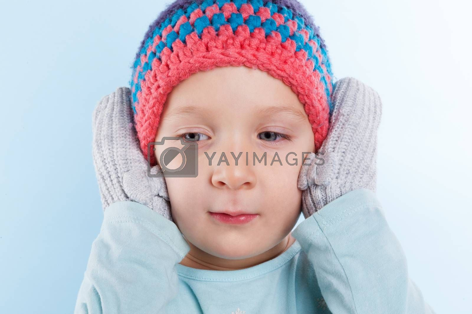 Cute baby girl in gloves covering her ears and hat isolated on light blue background. Winter season.