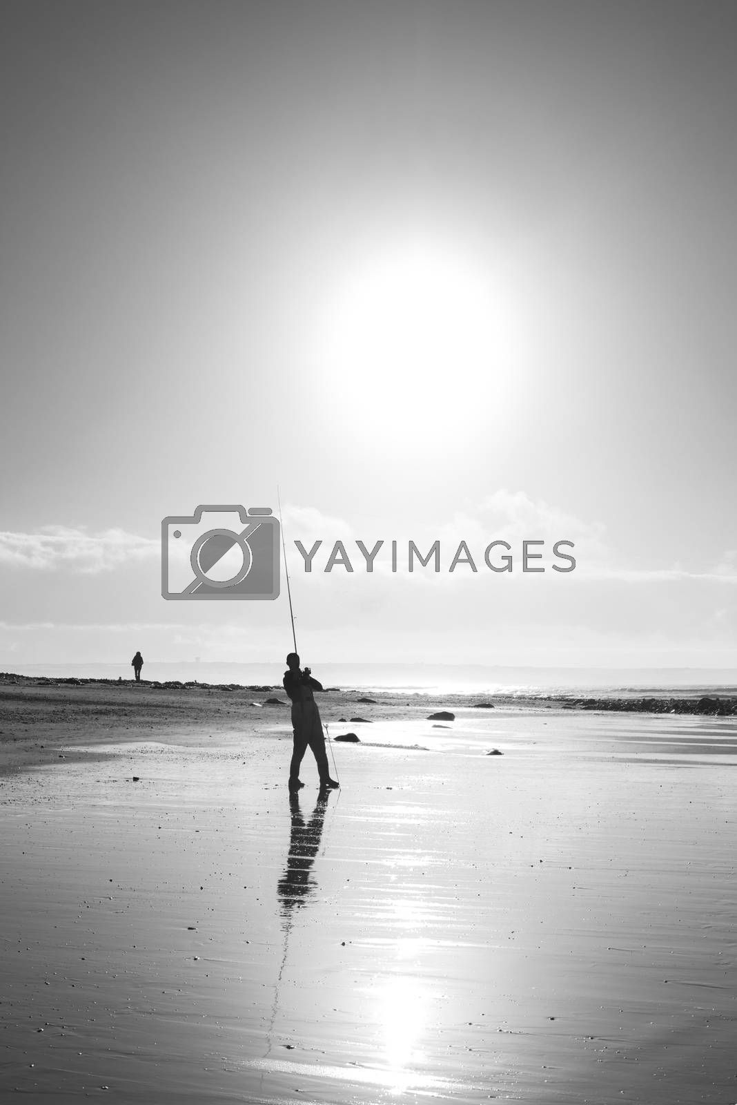 lone fisherman fishing on the beach in Ballybunion county Kerry Ireland in black and white