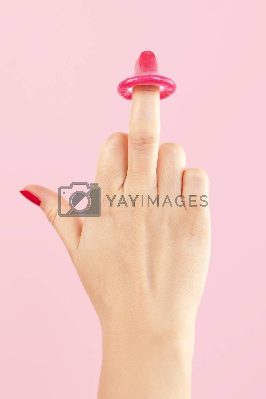 Female hand with red nails holding pink condom isolated on pink background. Safe sex and birth control concept.