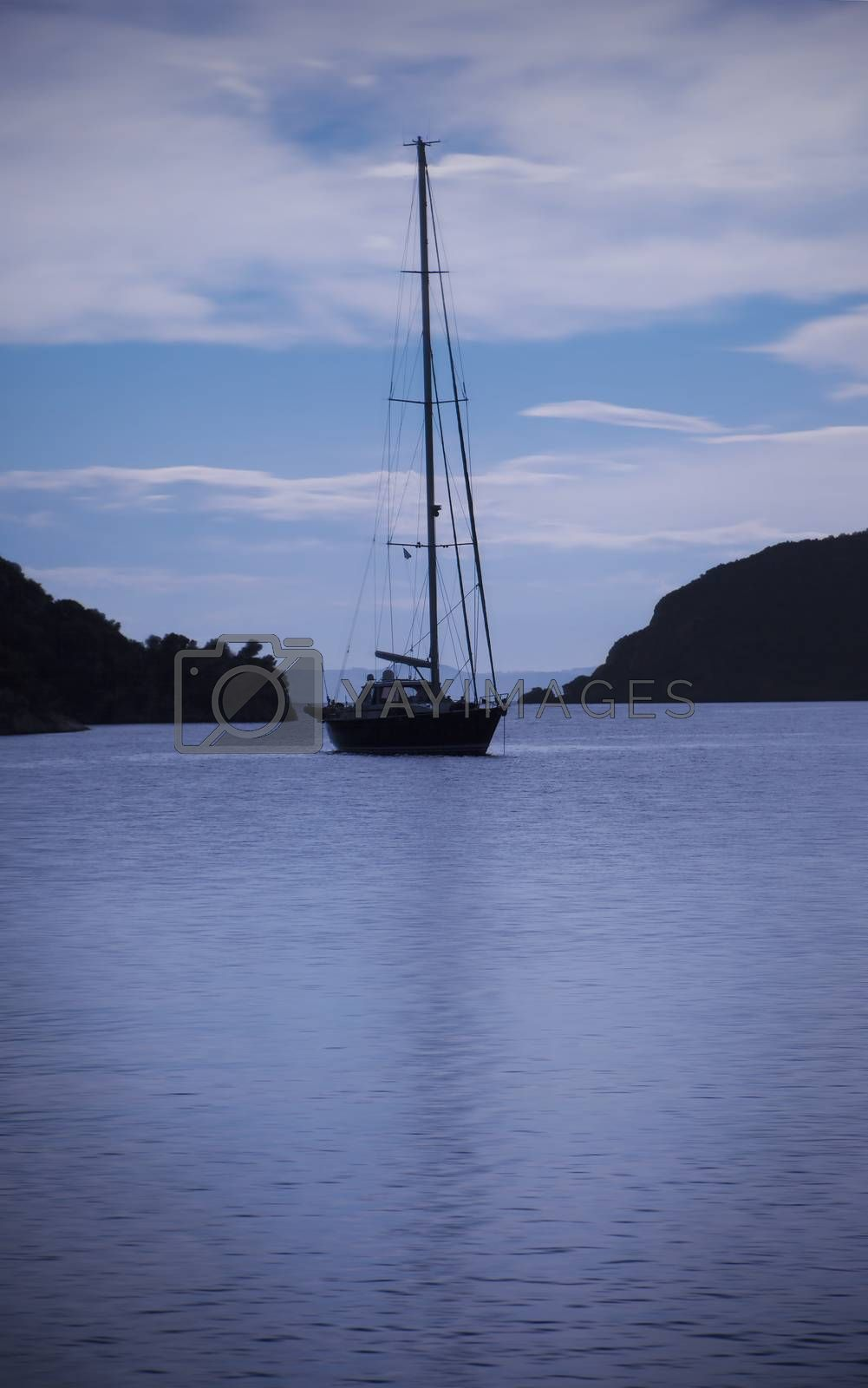 Yacht, mooring in a calm sea or ocean bay water in early blue lit morning.