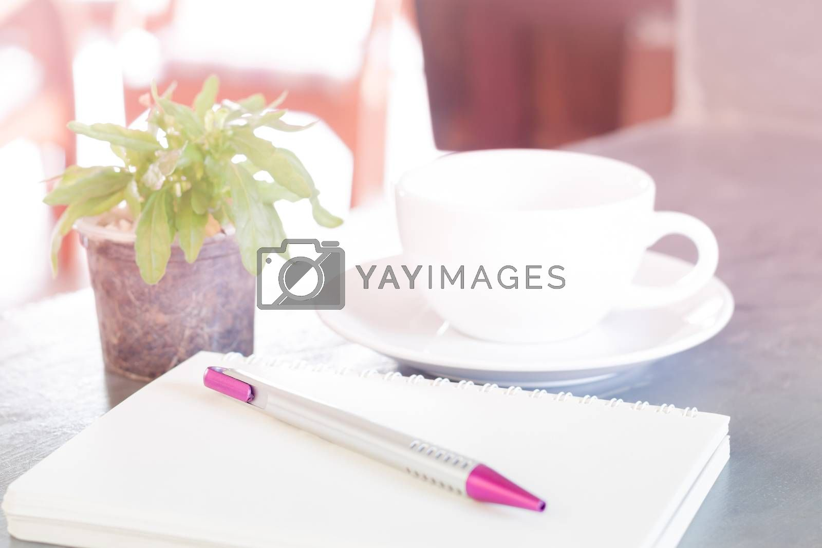 Royalty free image of Notepad, pen and green plant on grey background by punsayaporn