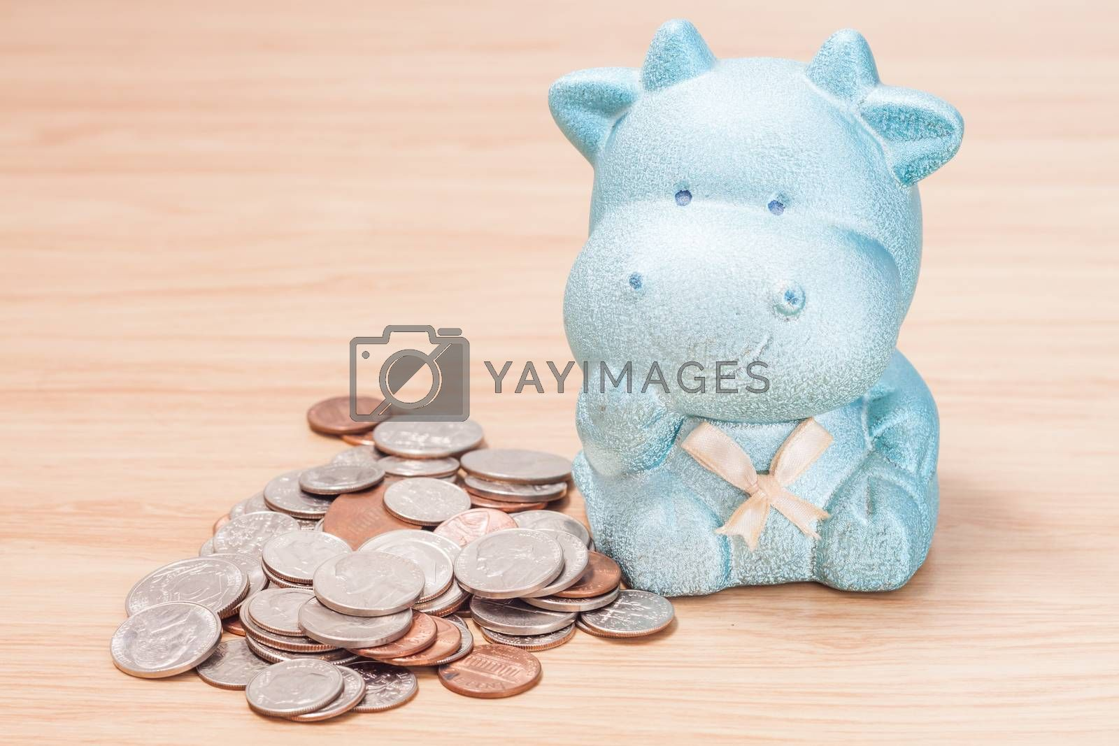 Royalty free image of Green cow doll saving box with coins by punsayaporn