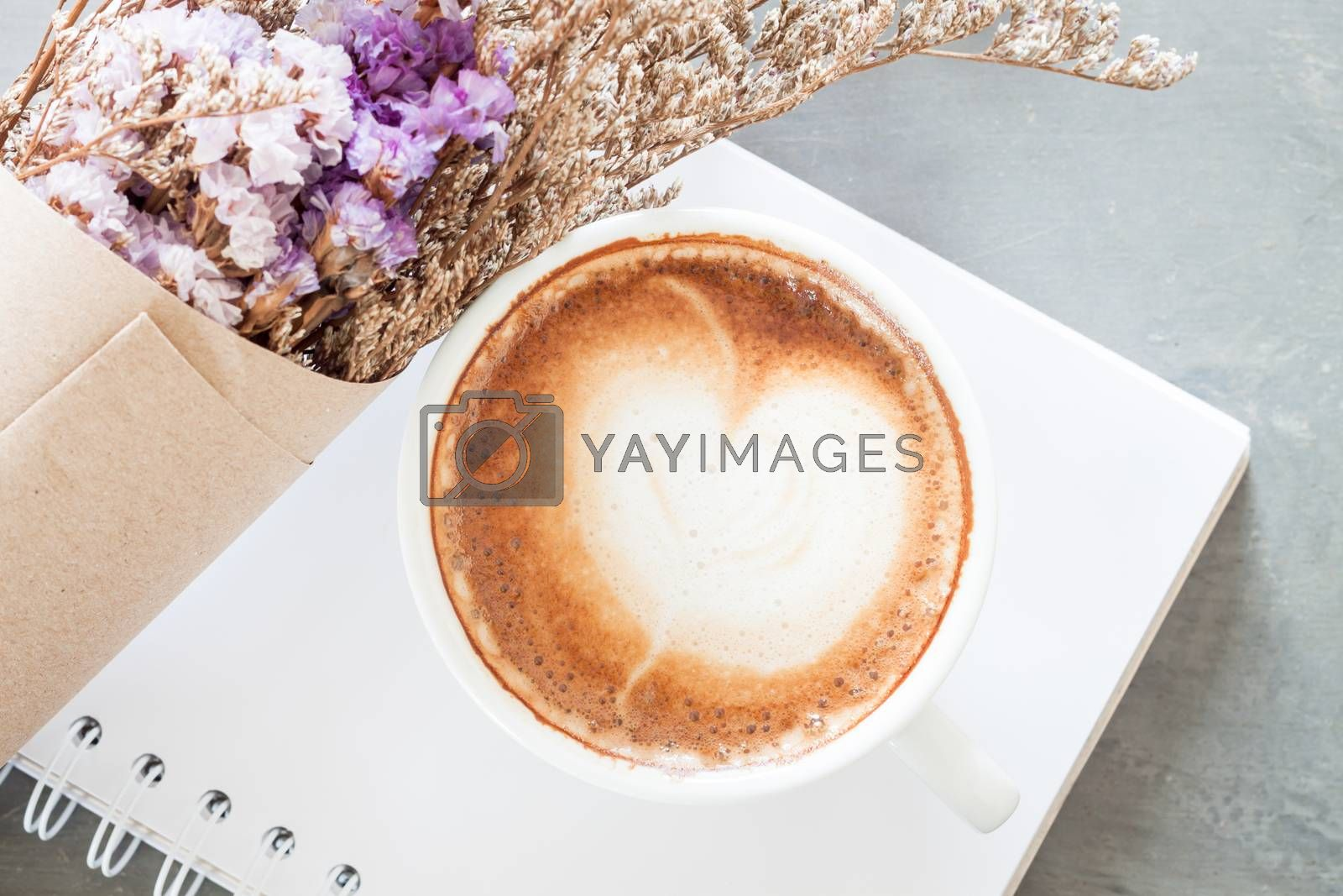 Royalty free image of Coffee cup with beautiful violet flower by punsayaporn