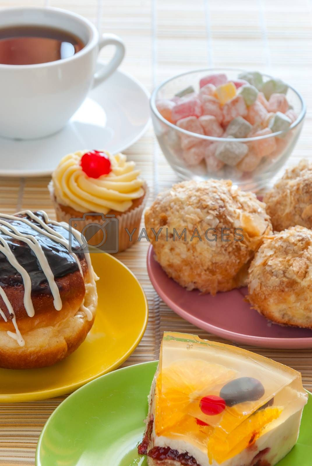 Tea, fresh cherry muffin, colorful delight, eclair and doughnut, various sweet dessert
