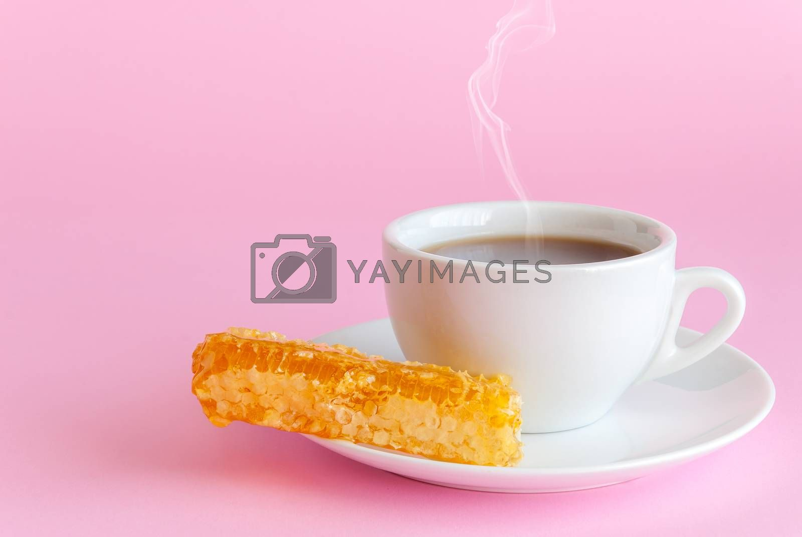 Cup of hot tea and honeycomb on pink background
