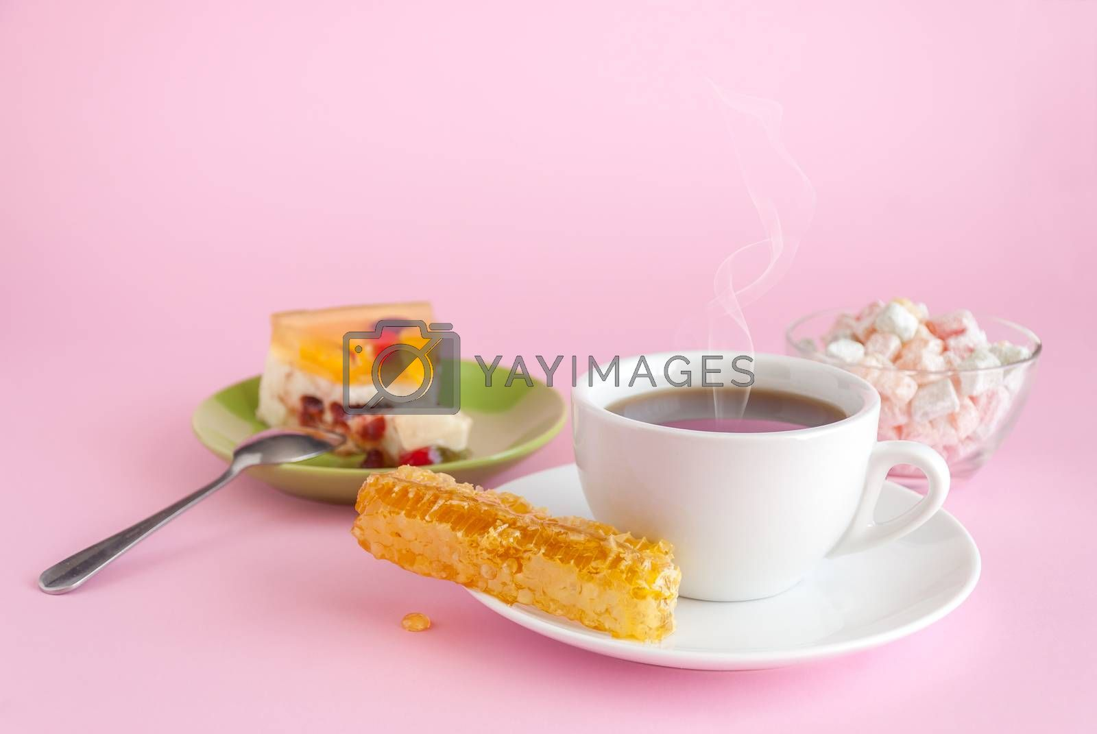 Cup of hot tea, honeycomb and cake on pink background