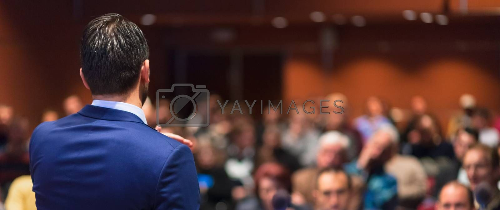 Rear view of speaker giving a talk on corporate Business Conference. Audience at the conference hall. Business and Entrepreneurship event. Panoramic composition.
