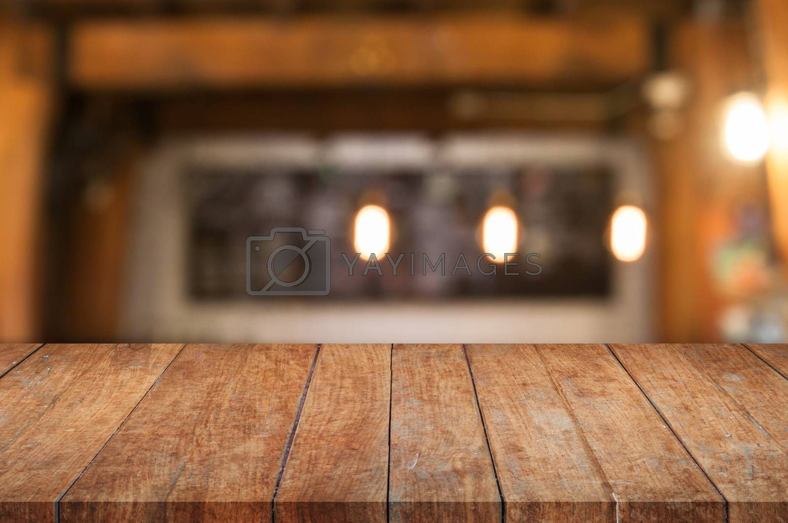 Royalty free image of Brown wooden table top with coffee shop by punsayaporn