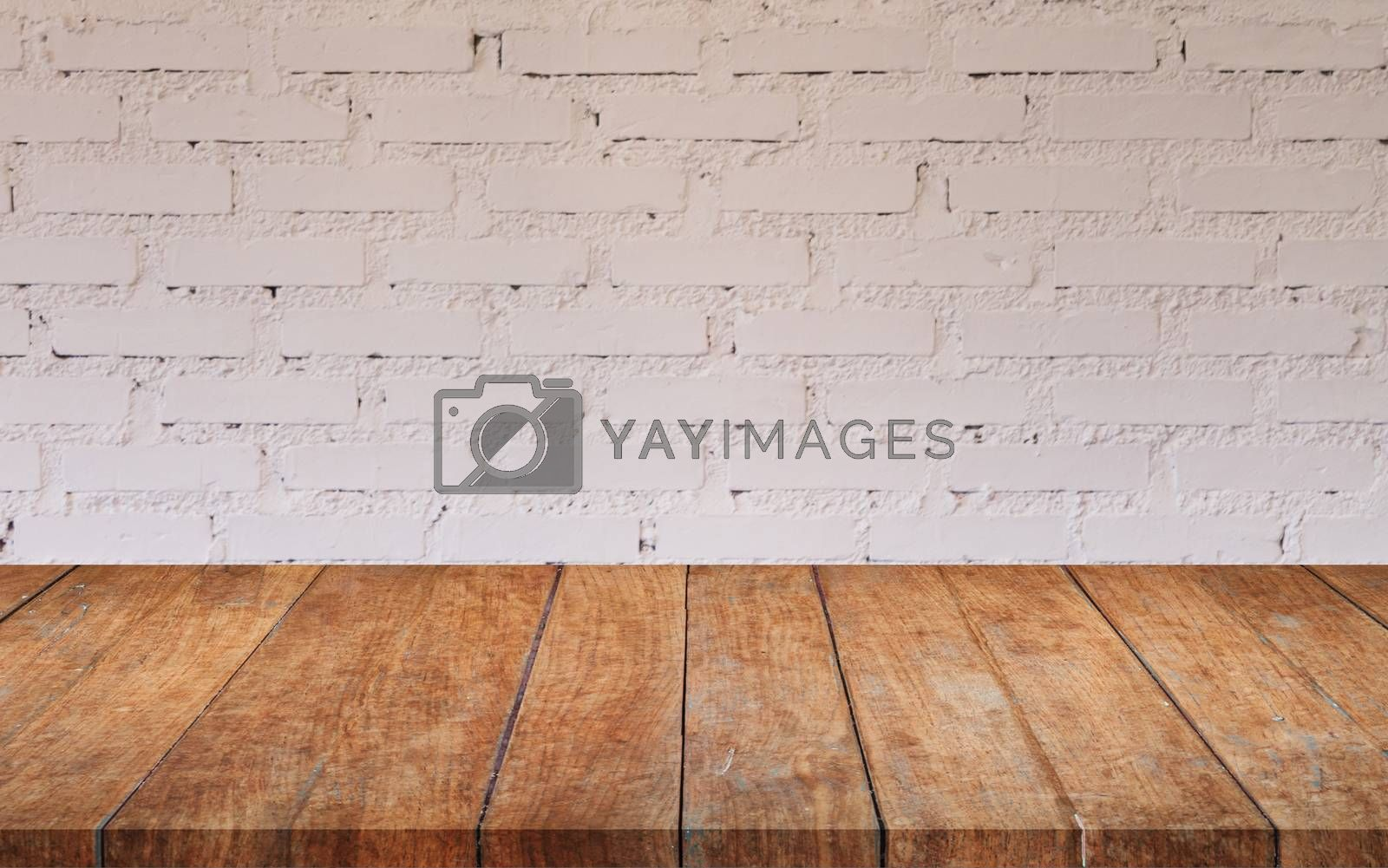 Royalty free image of Brown wooden table top with white brick wall by punsayaporn