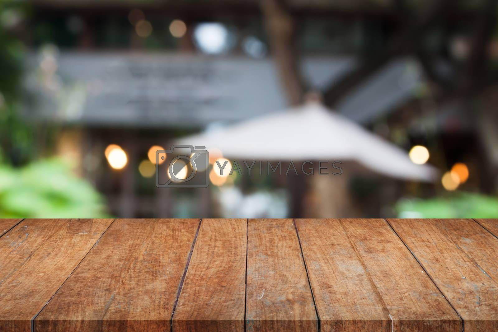 Royalty free image of Perspective brown wooden table top with cafe background by punsayaporn
